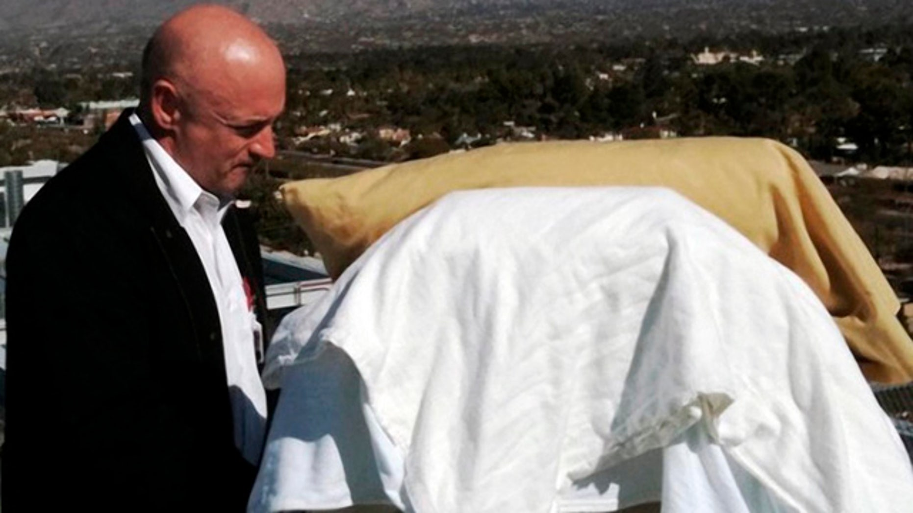 In this photo provided by the office of U.S. Rep Gabrielle Giffords, Giffords' husband, Mark Kelly, stands with his wife as she looks from her bed at the Santa Catalina Mountains while on an outdoor deck at University Medical Center in Tucson, Ariz., Thursday, Jan. 20, 2011. Giffords is scheduled to be flown to Houston on Friday to begin her rehabilitation. (AP Photo/Office of U.S. Rep. Gabrielle Giffords)