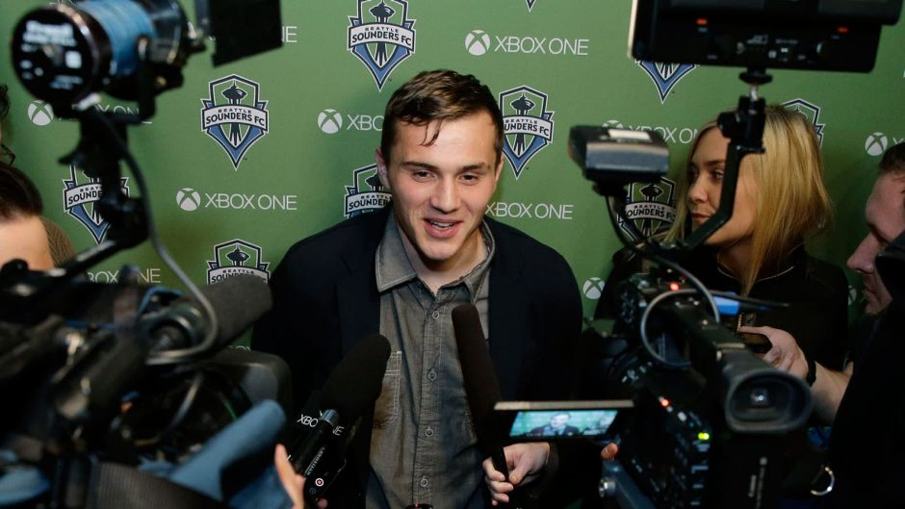 Jordan Morris talks to reporters Thursday, Jan. 21, 2016, in Seattle after the MLS soccer Seattle Sounders FC announced his signing as a forward. Morris, who played for Stanford, was the Hermann Trophy winner in 2015 as the top college player in the country. (AP Photo/Ted S. Warren)
