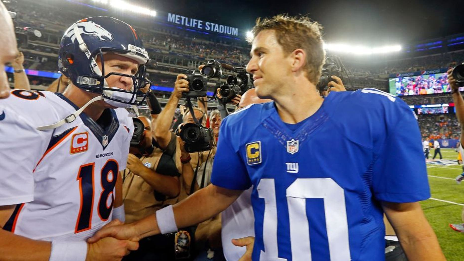 EAST RUTHERFORD, NJ - SEPTEMBER 15: (NEW YORK DAILIES OUT) Quarterbacks Peyton Manning #18 of the Denver Broncos and Eli Manning #10 of the New York Giants meet after their game on September 15, 2013 at MetLife Stadium in East Rutherford, New Jersey. The Broncos defeated the Giants 41-23. (Photo by Jim McIsaac/Getty Images)