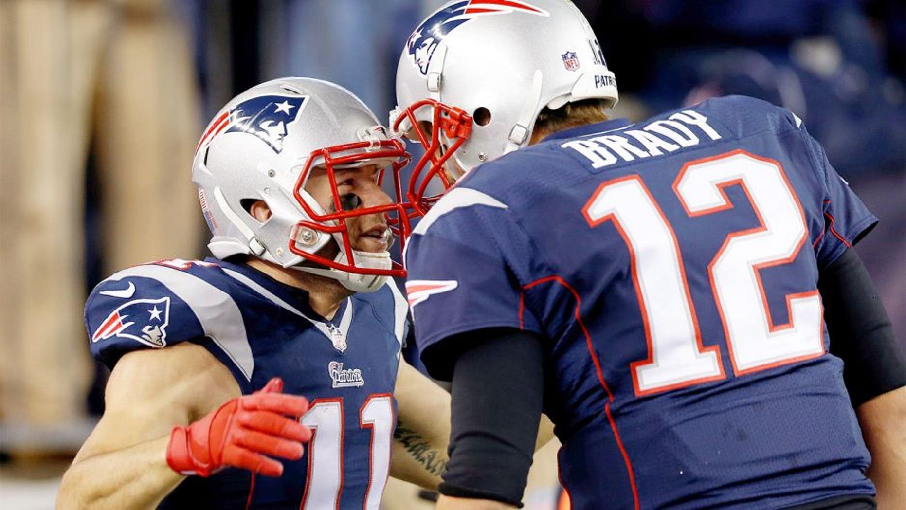 Nov 2, 2014; Foxborough, MA, USA; New England Patriots quarterback Tom Brady (12) congratulates special teams Julian Edelman (11) on scoring a touchdown on a run back return during the second quarter against the Denver Broncos at Gillette Stadium. Mandatory Credit: Greg M. Cooper-USA TODAY Sports