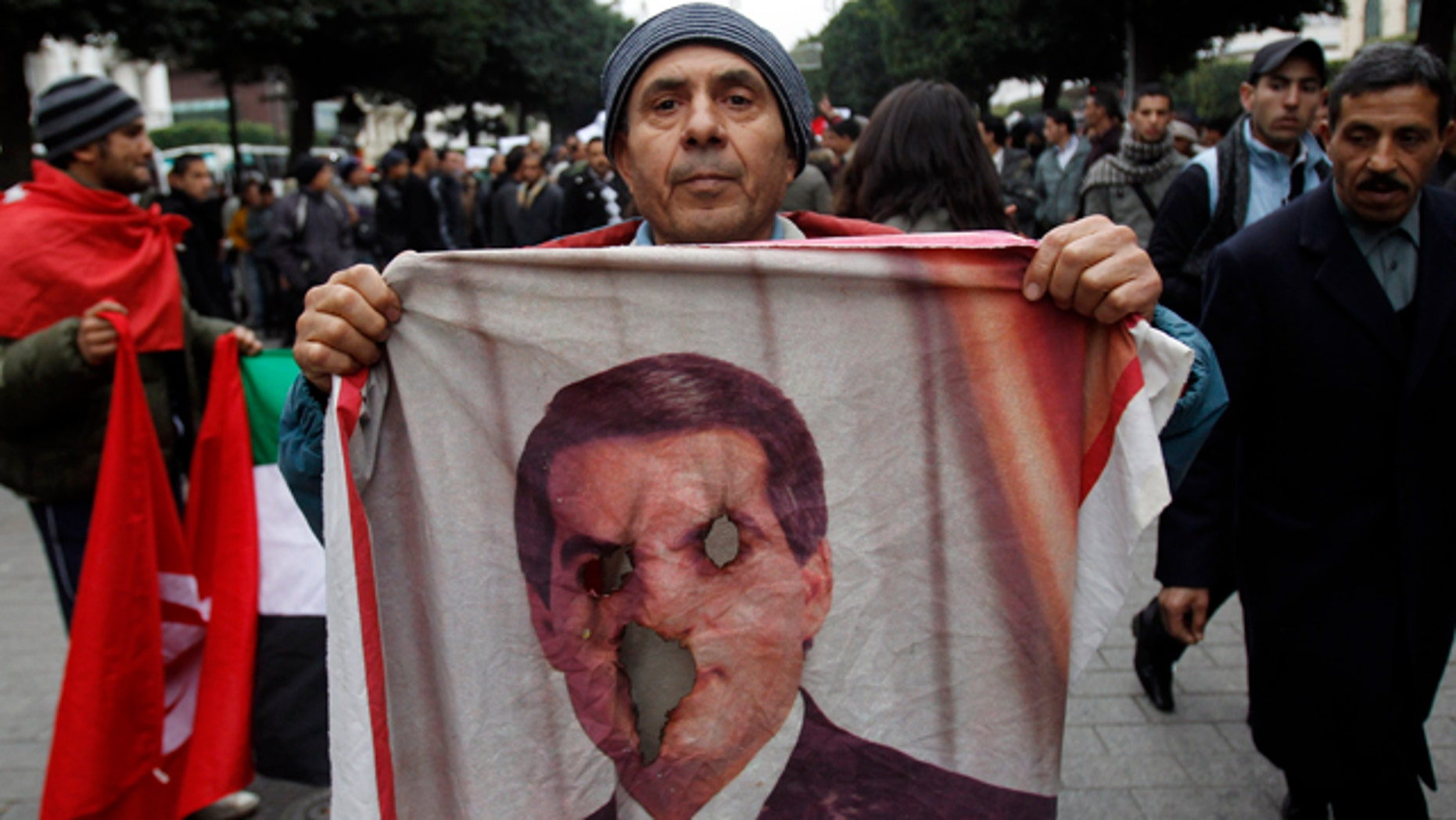 Jan. 25: A protestor holds a burned picture of former Tunisian President Zine El Abidine Ben Ali during a demonstration in Tunis.