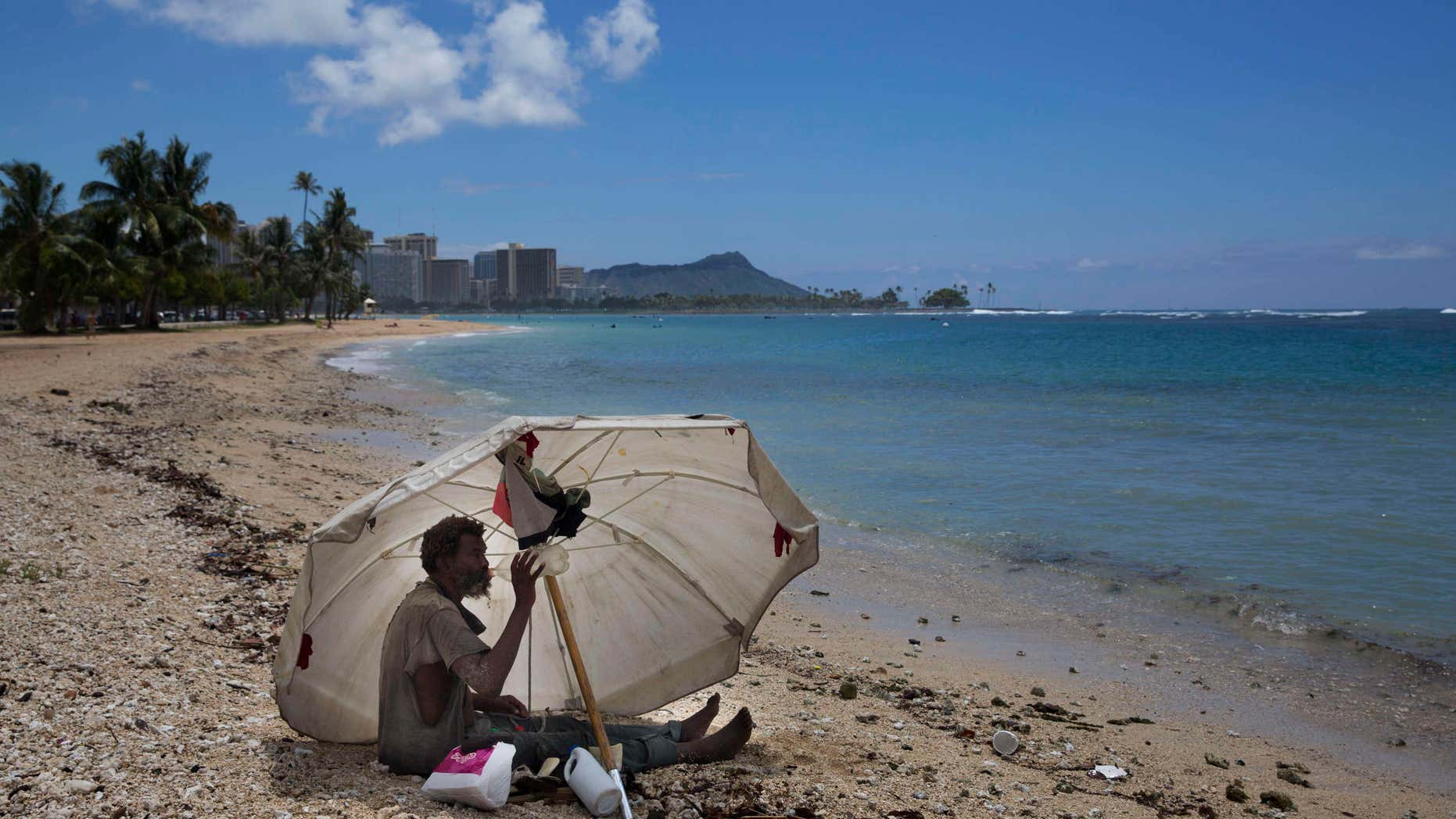 FILE - In this Aug. 27, 2015, file photo, a homeless man drinks water while sitting on the beach at Ala Moana Beach Park located near Waikiki in Honolulu.