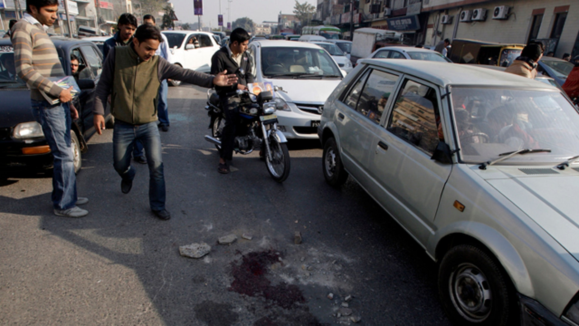 Jan. 27: People look at blood stains at a roadside in Lahore, Pakistan.
