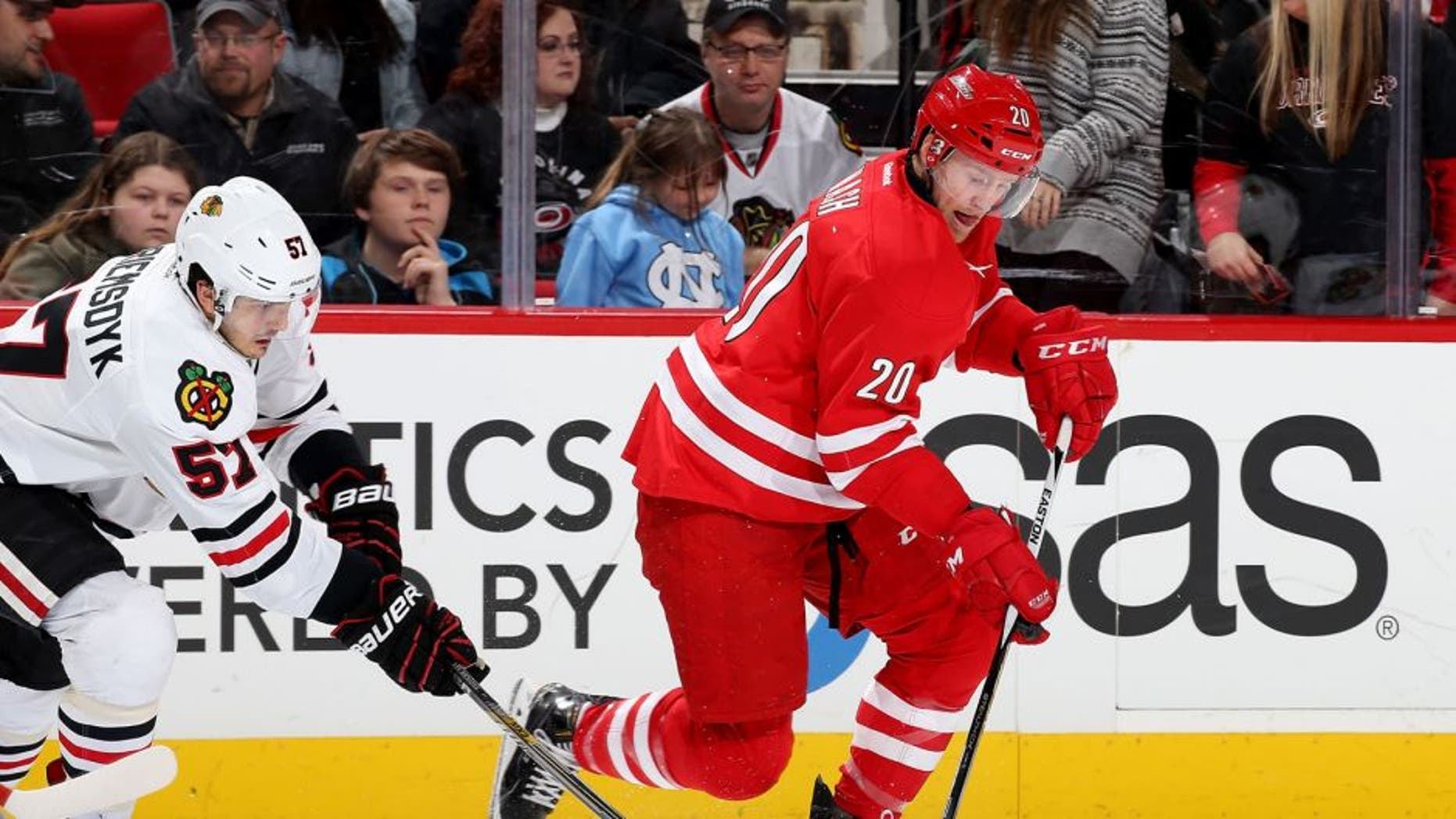 RALEIGH, NC - JANUARY 26: Riley Nash #20 of the Carolina Hurricanes gets out on a breakaway as Trevor van Riemsdyk #57 of the Chicago Blackhawks steals the puck during an NHL game at PNC Arena on January 26, 2016 in Raleigh, North Carolina. (Photo by Gregg Forwerck/NHLI via Getty Images)