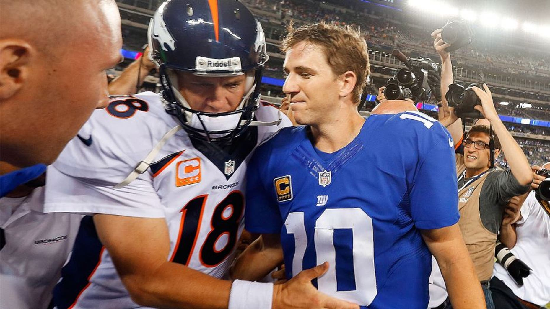EAST RUTHERFORD, NJ - SEPTEMBER 15: (NEW YORK DAILIES OUT) Quarterbacks Peyton Manning #18 of the Denver Broncos and Eli Manning #10 of the New York Giants meet after their game on September 15, 2013 at MetLife Stadium in East Rutherford, New Jersey. The Broncos defeated the Giants 41-23. (Photo by Jim McIsaac/Getty Images) *** Local Caption *** Peyton Manning; Eli Manning