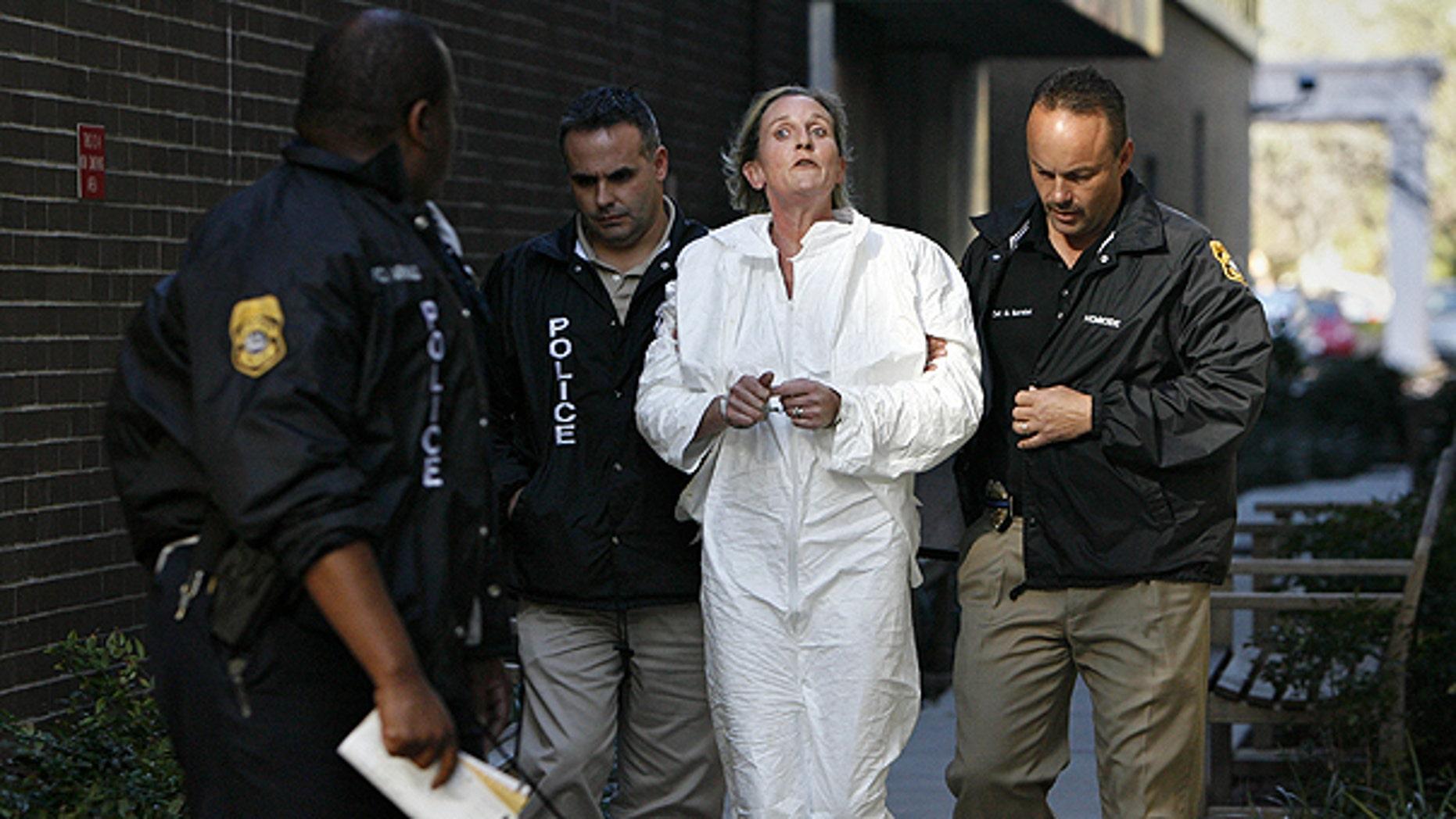 Jan. 28: Tampa Police officer escorts Julie Powers Schenecker to Orient Road Jail in Tampa, Fla.