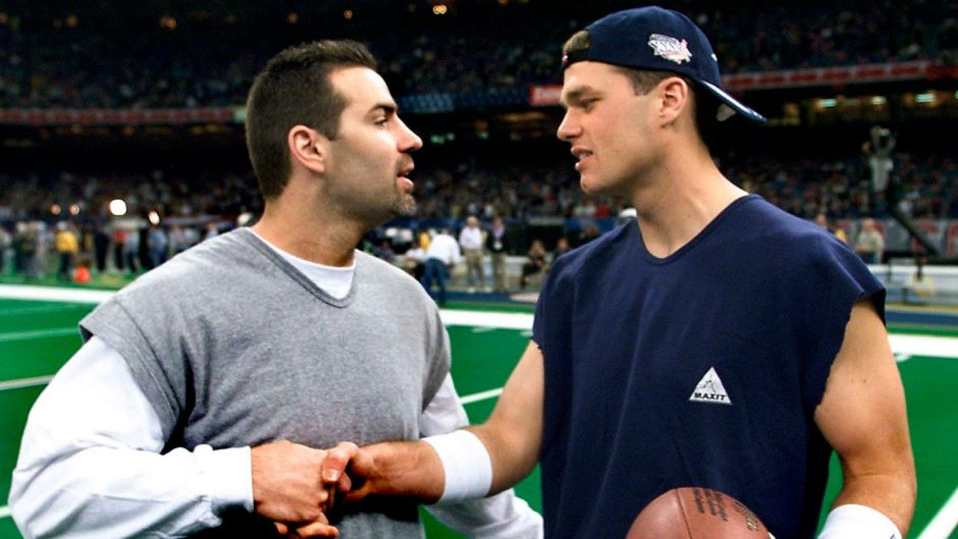 NEW ORLEANS, UNITED STATES: New England Patriots quarterback Tom Brady (R) chats with St. Louis Rams quarterback Kurt Warner (L) 03 February, 2002 at the Louisiana Superdome before Super Bowl XXXVI in New Orleans, Louisiana. The St. Louis Rams and the New England Patriots are playing for the NFL championship. AFP PHOTO/Jeff HAYNES. (Photo credit should read JEFF HAYNES/AFP/Getty Images)