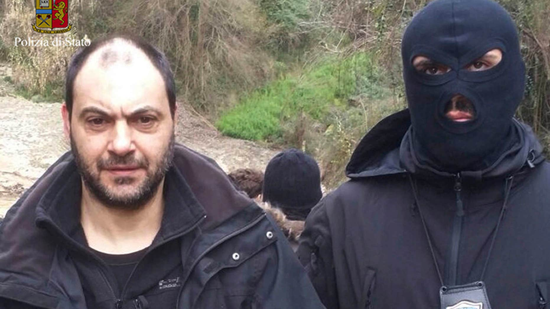 In this photo released by the Italian Police Friday, Jan. 29, 2016, Giuseppe Ferraro is taken into custody after he was arrested in a bunker.