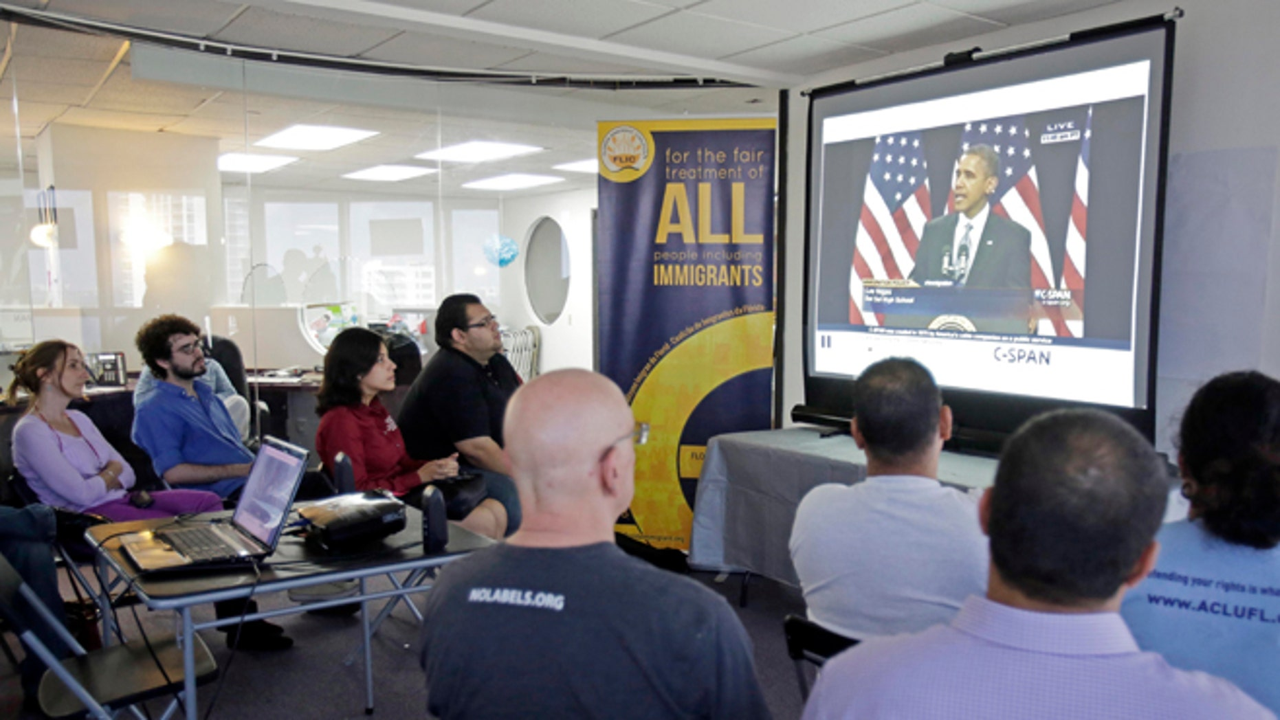 Jan. 29, 2013: Illegal immigrants and immigration activists watch a live image of President Barack Obama speaking about immigration reform as they sit together in Miami.