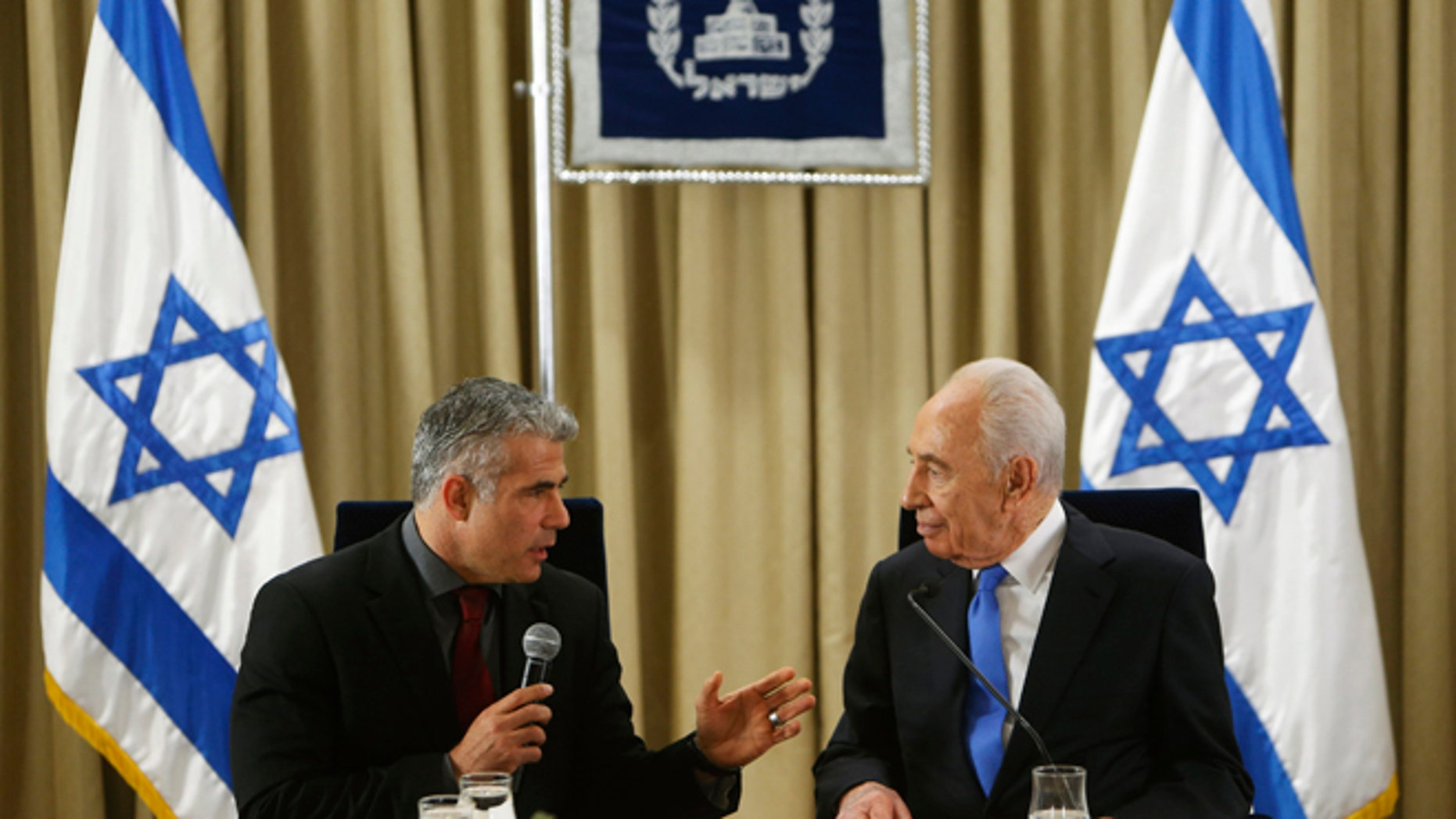 Jan. 30, 2013: Israel's President Shimon Peres, right, listens as Yair Lapid, leader of the Yesh Atid (There is a Future) party, speaks during their meeting in Jerusalem.