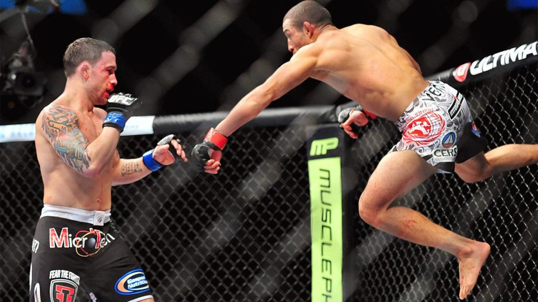 Feb 2, 2013; Las Vegas, NV, USA; Frankie Edgar (left) and Jose Aldo (right) battle each other during UFC 156 at the Mandalay Bay Events Center. Mandatory Credit: Gary A. Vasquez-USA TODAY Sports