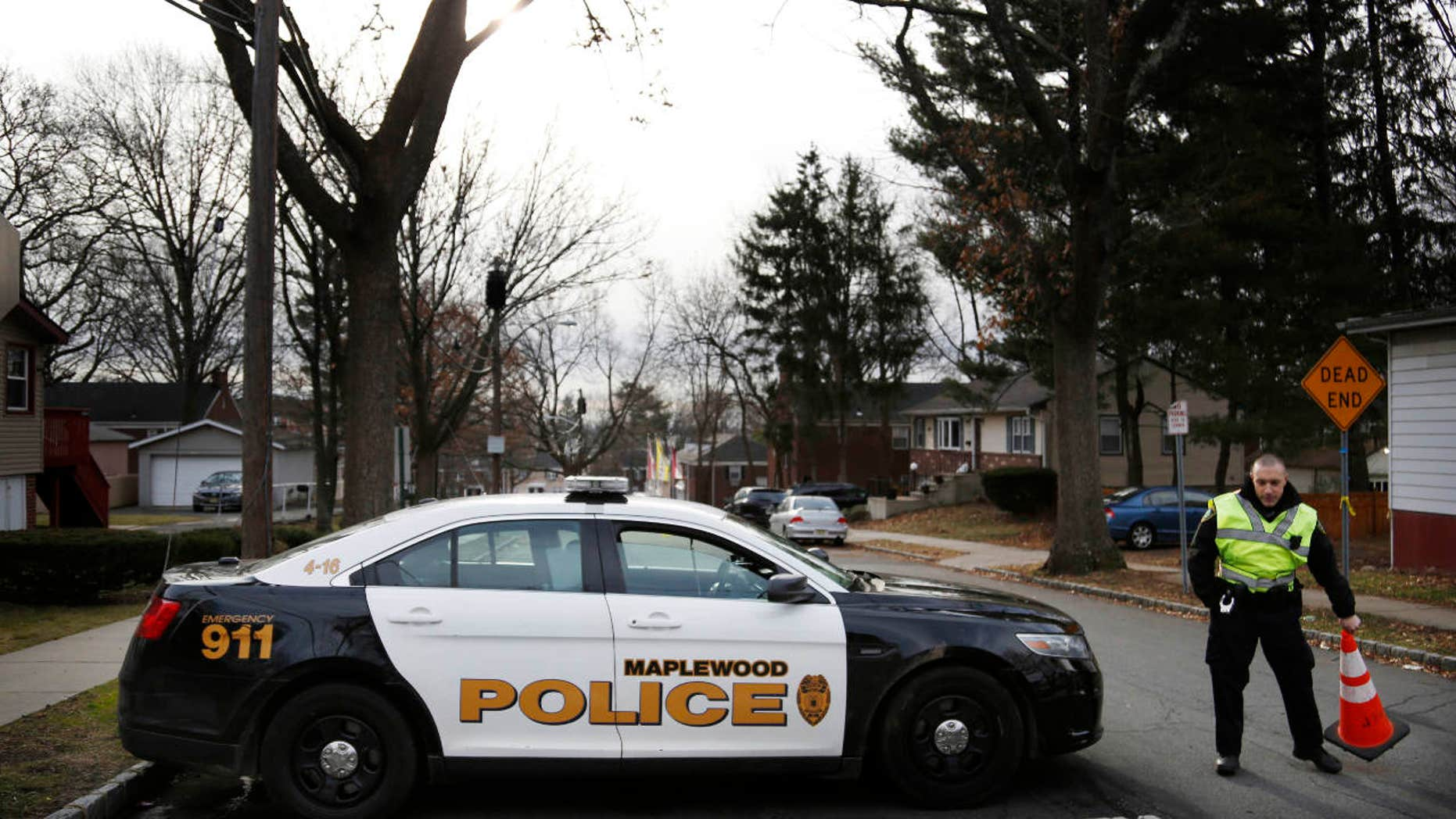 A police officers blocks the entrance to Van Ness Court in Maplewood, N.J., Monday, Jan. 30, 2017, the day after three people were found dead in an apartment there.