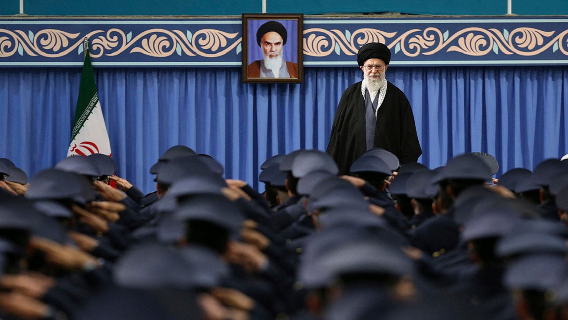 Supreme Leader Ayatollah Ali Khamenei stands as army air force and air defense salute at the start of their meeting in Tehran, Iran, Feb. 8, 2018. A portrait of the late revolutionary founder Ayatollah Khomeini hangs in the background.