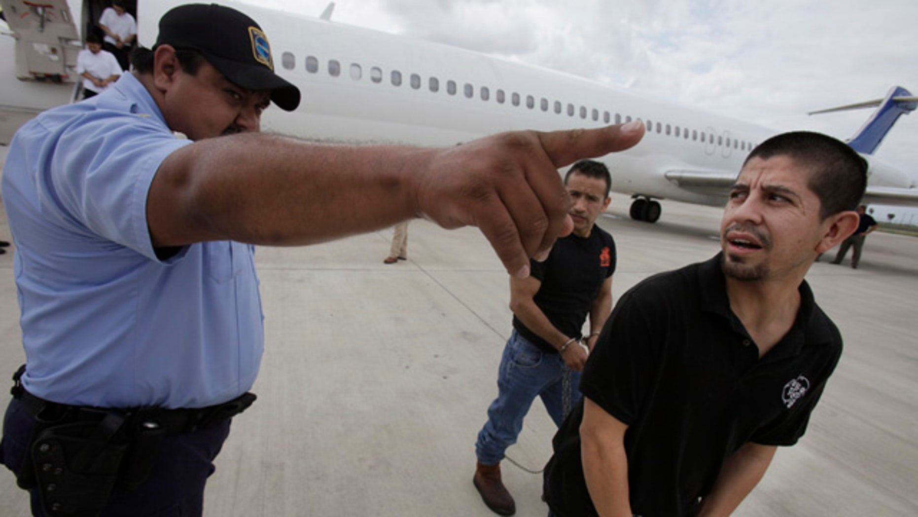 Shackled Mexican immigrants are directed by a guard to a waiting deportation by the U.S. Immigration and Customs Enforcement in Harlingen, Texas.