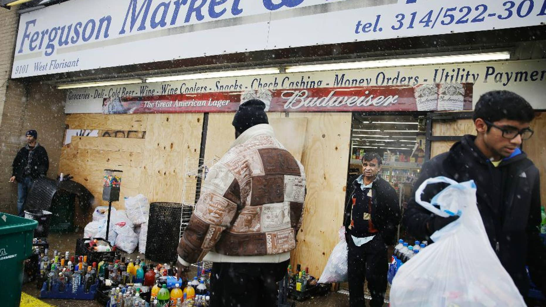 FILE - In this Wednesday, Nov. 26, 2014, file photo, Kush Patel, right, carries out bags of merchandise while helping his uncle Andy Patel, rear, clean up the looting damage from Monday's riots at his store, Ferguson Market and Liquor, in Ferguson, Mo. The store is disputing a new documentary's claims that surveillance video suggests Michael Brown didn't rob the store before he was fatally shot by police in Ferguson. One of the filmmakers said he believes the footage shows Brown trading marijuana for a bag of cigarillos early on Aug. 9, 2014, and that Brown intended to come back later for the cigarillos. Store officials said no drug transaction took place and Brown stole the cigarillos while at the store later that day. (AP Photo/David Goldman, File)