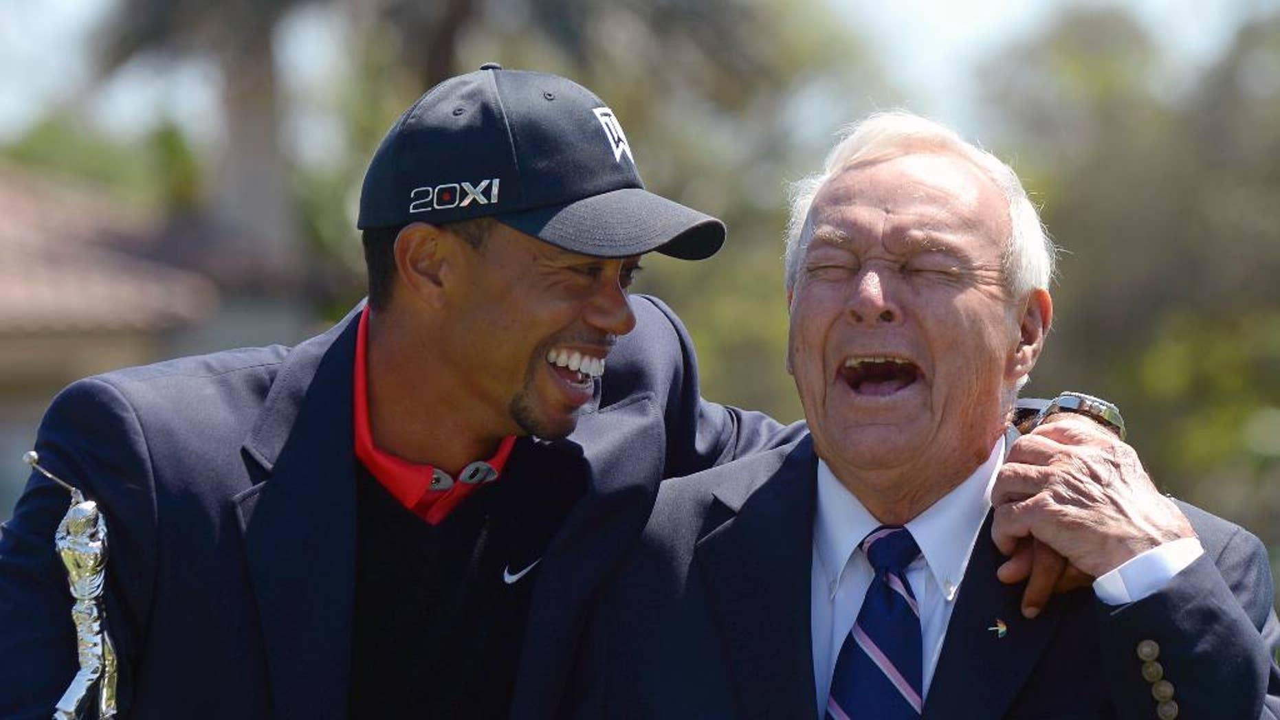 FILE - In this Monday, March 25, 2013 file photo, Tiger Woods, left, and Arnold Palmer share a laugh during the trophy presentation after Woods won the Arnold Palmer Invitational golf tournament in Orlando, Fla. Tiger Woods won't be at the Arnold Palmer Invitational next week and still doesn't know when he will play again. Woods announced on his website Thursday night, March 9, 2017 that ongoing rest and rehabilitation on his back will keep him away from Bay Hill and the tournament he has won a record eight times. (AP Photo/Phelan M. Ebenhack, File)