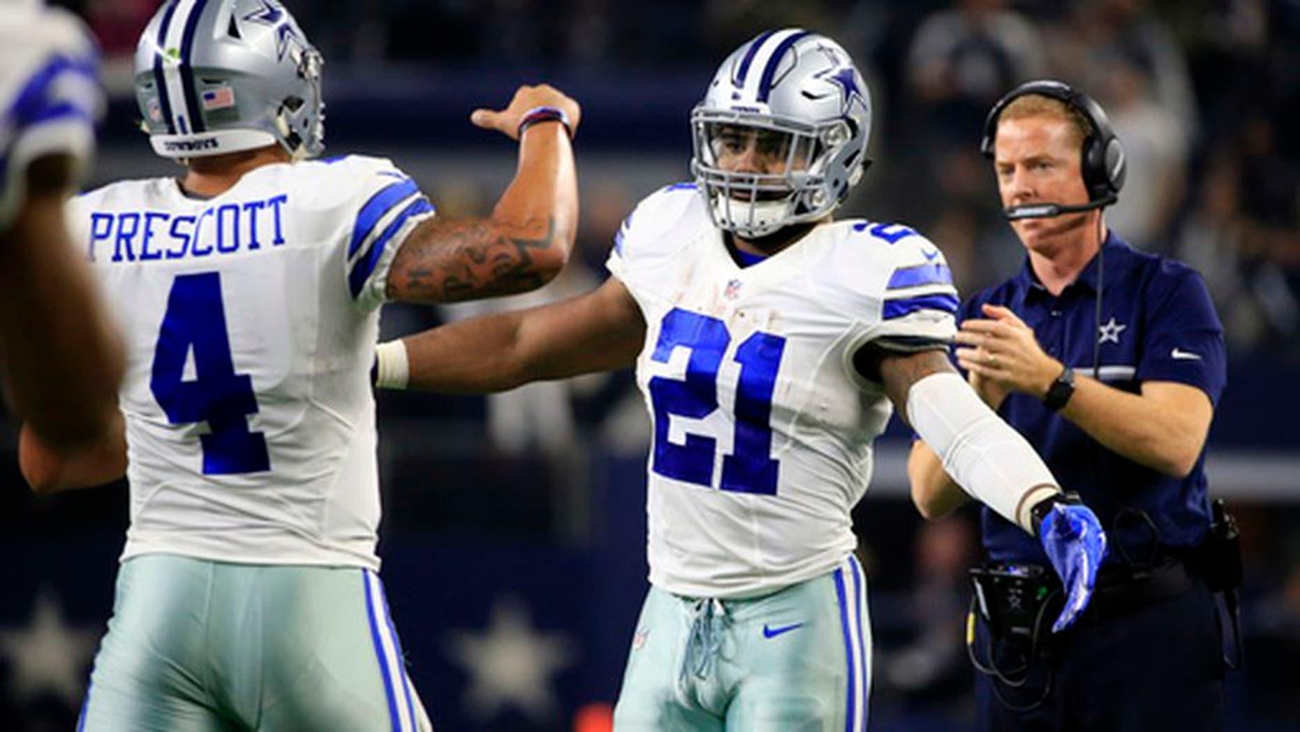 Dallas Cowboys' Dak Prescott (4) is congratulated on his touchdown run by Ezekiel Elliott (21) in the first half of an NFL football game against the Tampa Bay Buccaneers as head coach Jason Garrett, right, watches, , Sunday, Dec. 18, 2016, in Arlington, Texas. (AP Photo/Ron Jenkins)