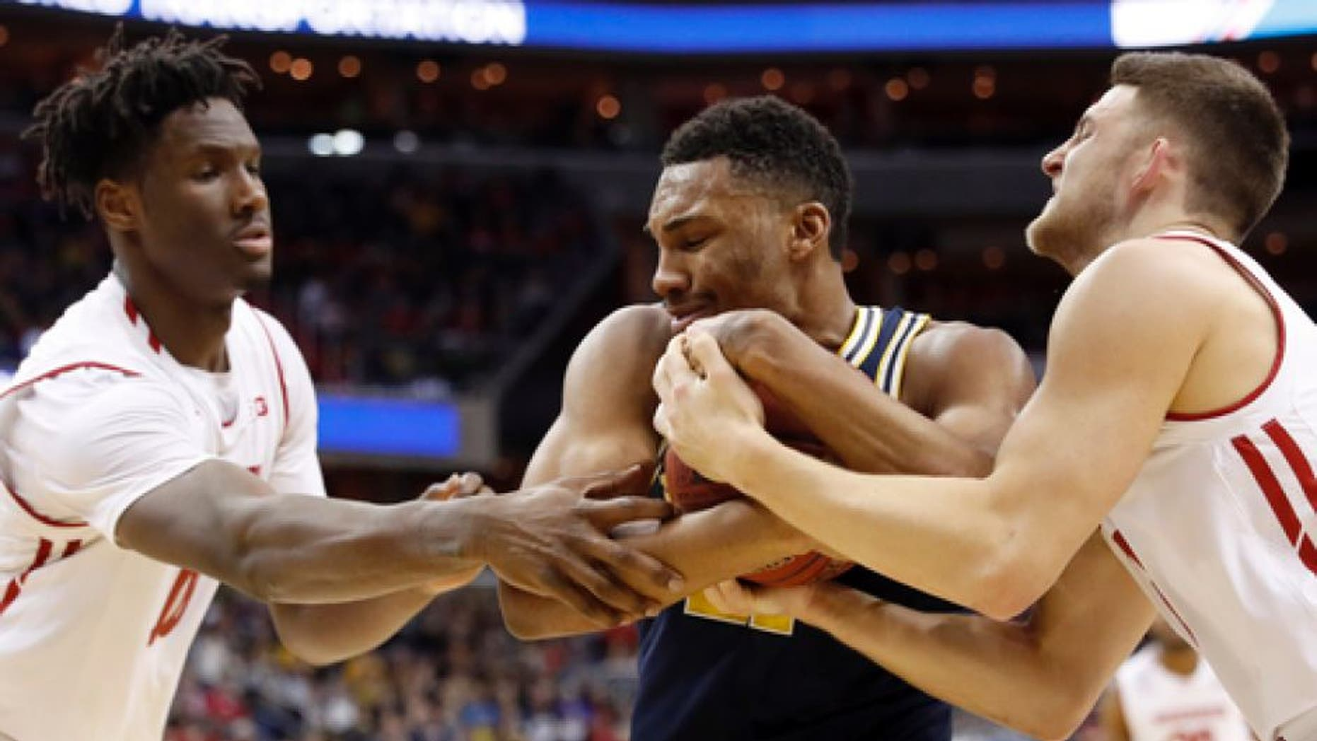 Wisconsin forward Nigel Hayes, left, Michigan guard Zak Irvin and Wisconsin guard Zak Showalter grab for the ball during the second half of the Big Ten NCAA college basketball championship game, Sunday, March 12, 2017, in Washington. (AP Photo/Alex Brandon)