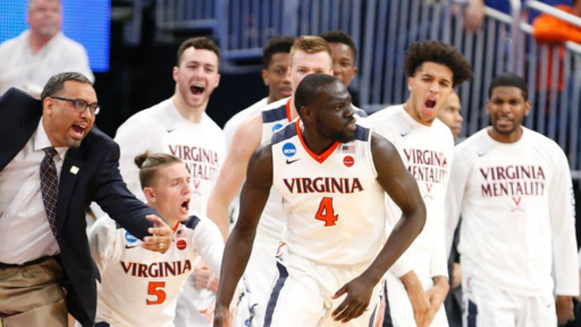 Players and coaches come off the bench as Virginia guard Marial Shayok (4) scores against UNC Wilmington during the second half of a first-round men's college basketball game in the NCAA Tournament, Thursday, March 16, 2017, in Orlando, Fla. Virginia defeated UNC Wilmington 76-71. (AP Photo/Wilfredo Lee)