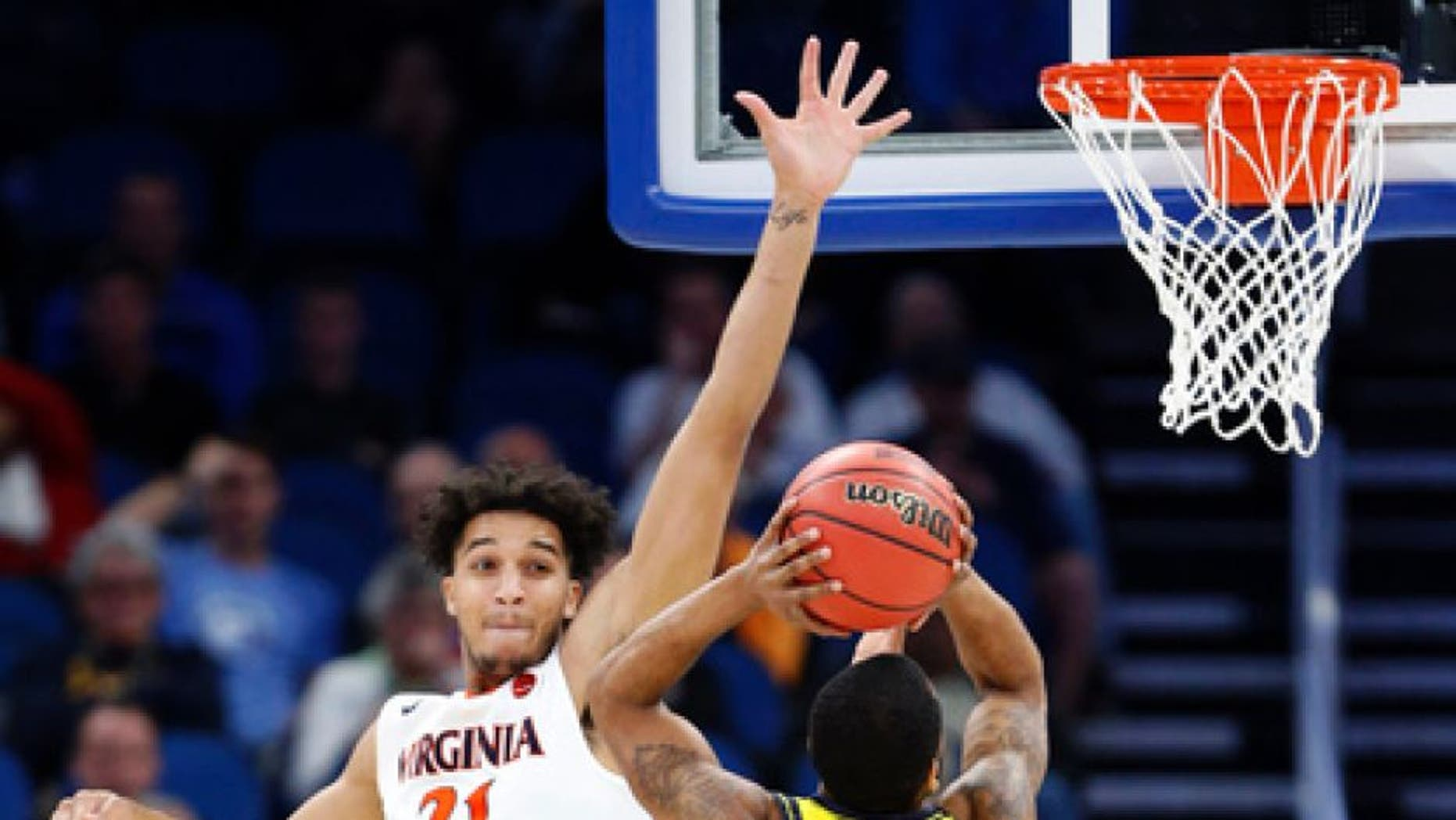UNC Wilmington guard Jordon Talley (4) goes up for a shot against Virginia forward Isaiah Wilkins (21) and guard Devon Hall during the first half of a first-round men's college basketball game in the NCAA Tournament, Thursday, March 16, 2017, in Orlando, Fla. Virginia defeated UNC Wilmington 76-71. (AP Photo/Wilfredo Lee)