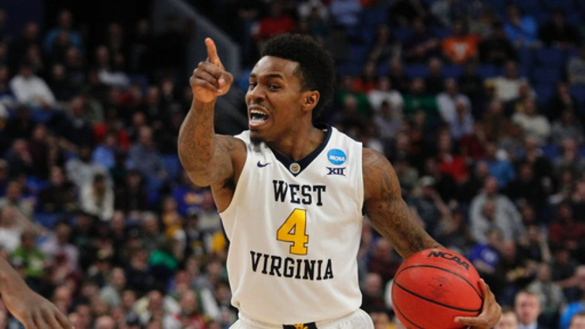 West Virginia guard Dexter Miles Jr. (4) directs his teammates during the second half of a first-round men's college basketball game against Bucknell in the NCAA Tournament, Thursday, March 16, 2017, in Buffalo, N.Y. (AP Photo/Jeffrey T. Barnes)