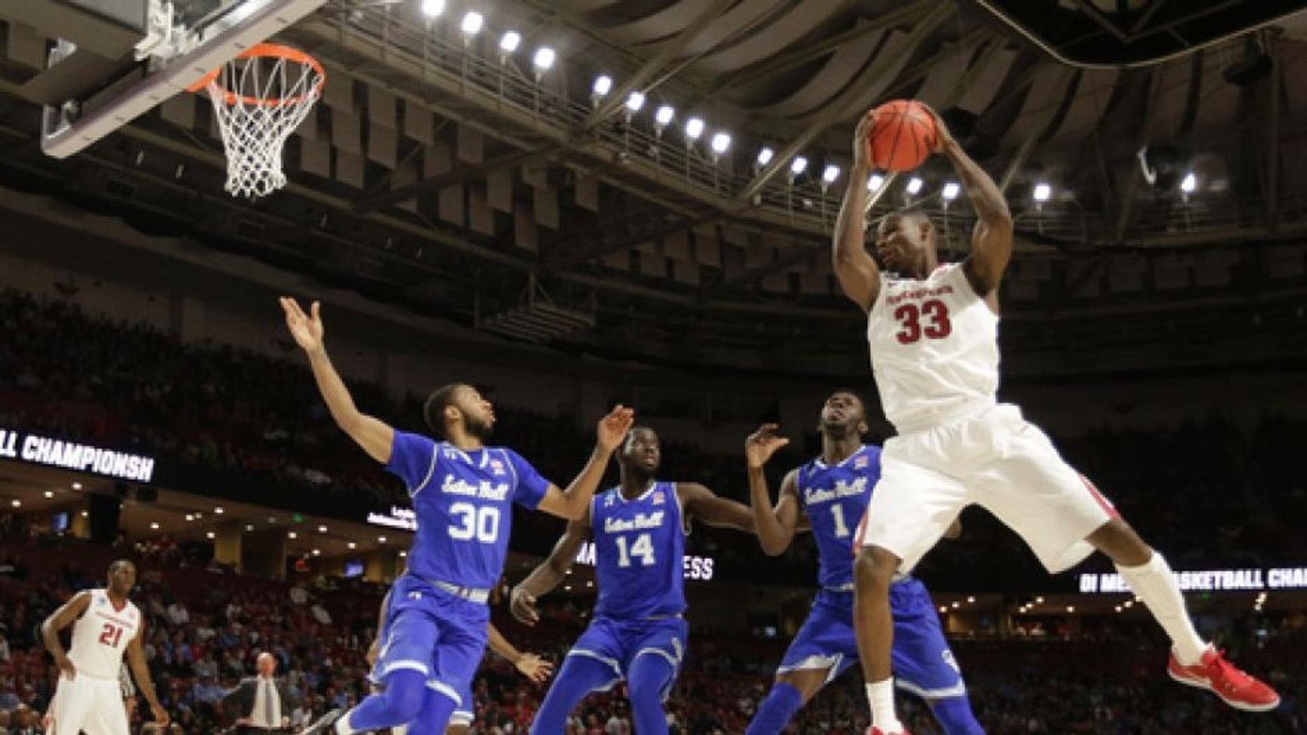 Arkansas's Moses Kingsley (33) grabs a rebound against Seton Hall players Madison Jones (30), Ismael Sanogo (14) and Michael Nzei (1) during the first half in a first-round game of the NCAA men's college basketball tournament in Greenville, S.C., Friday, March 17, 2017. (AP Photo/Chuck Burton)
