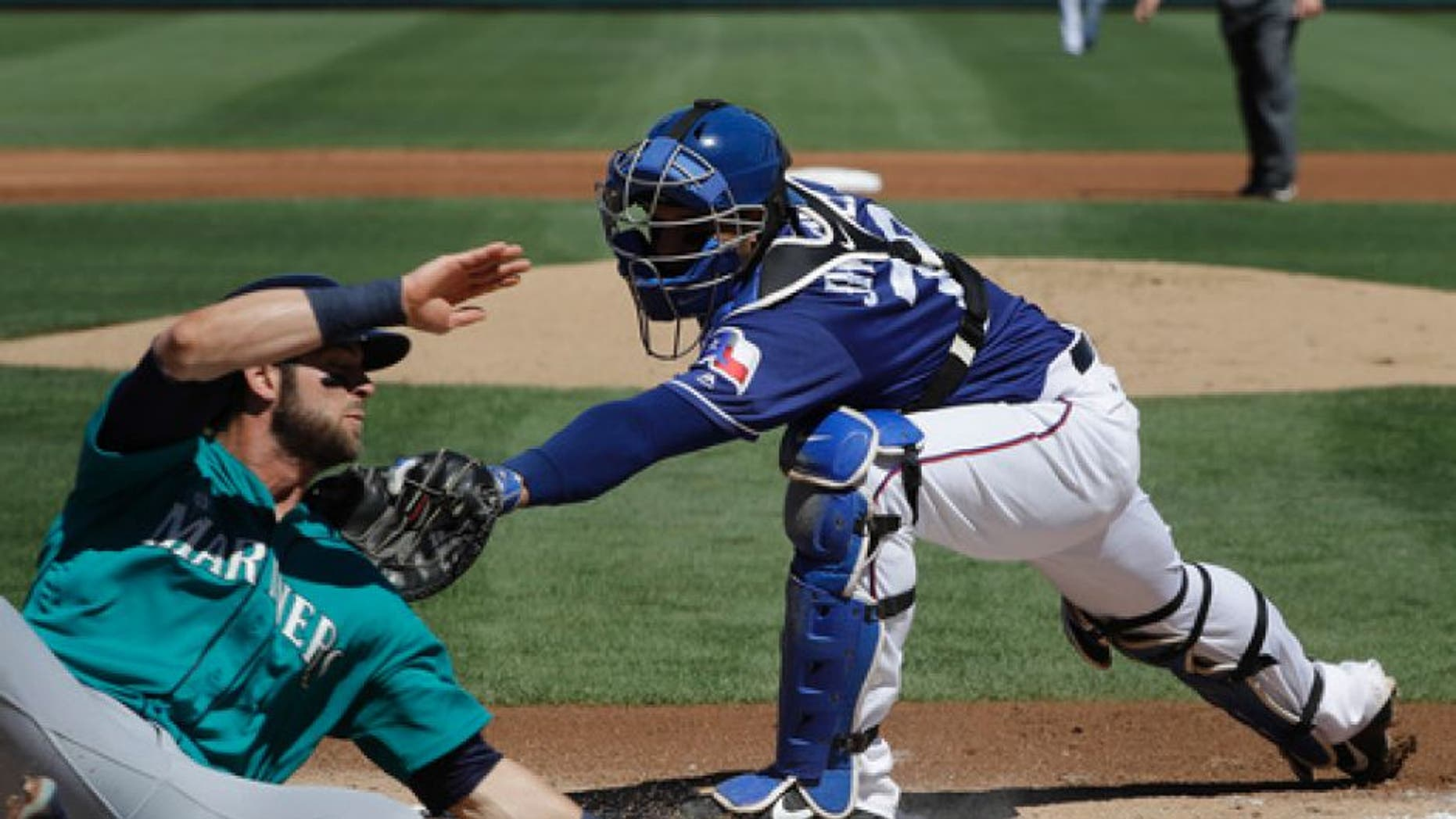 Texas Rangers catcher A.J. Jimenez tags out Seattle Mariners' Mitch Haniger during the first inning of a spring training baseball game Sunday, March 19, 2017, in Surprise, Ariz. (AP Photo/Darron Cummings)