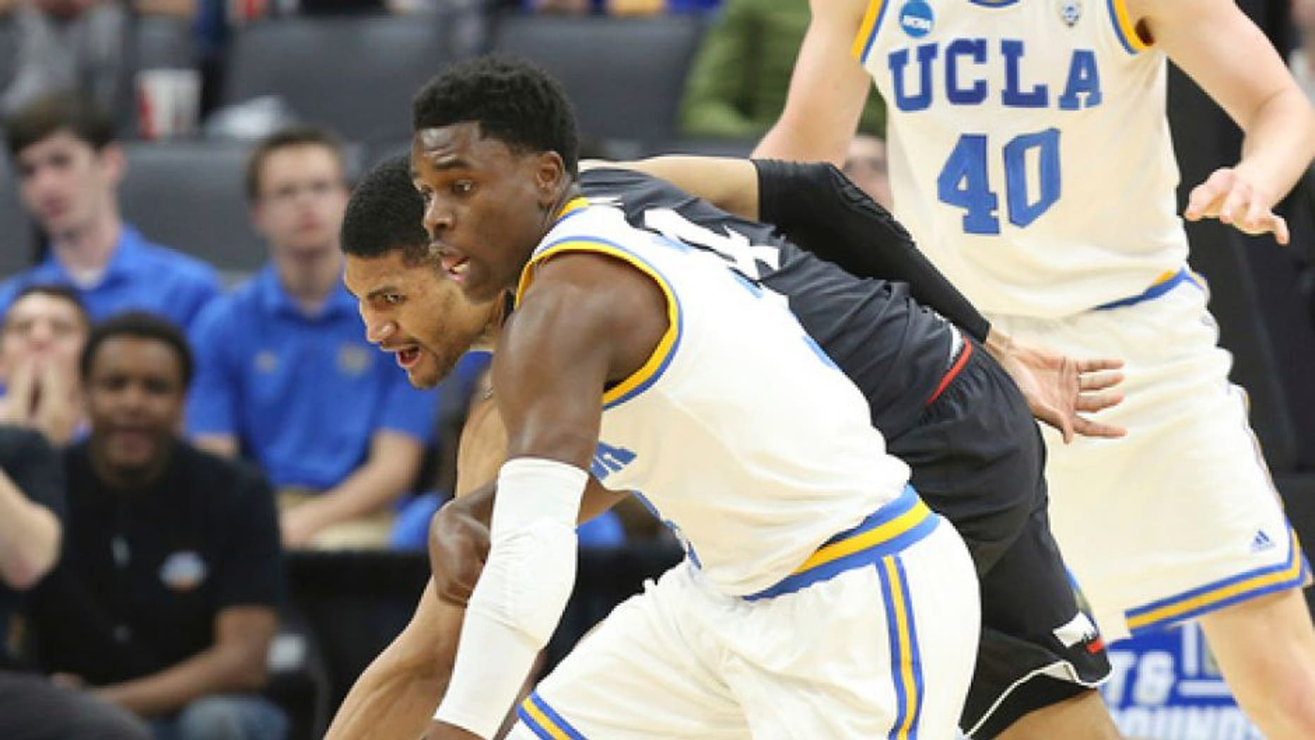UCLA guard Aaron Holiday, front, comes up with the ball against Cincinnati guard Jarron Cumberland during the first half of a second-round game of the NCAA men's college basketball tournament in Sacramento, Calif., Sunday, March 19, 2017. (AP Photo/Steve Yeater)