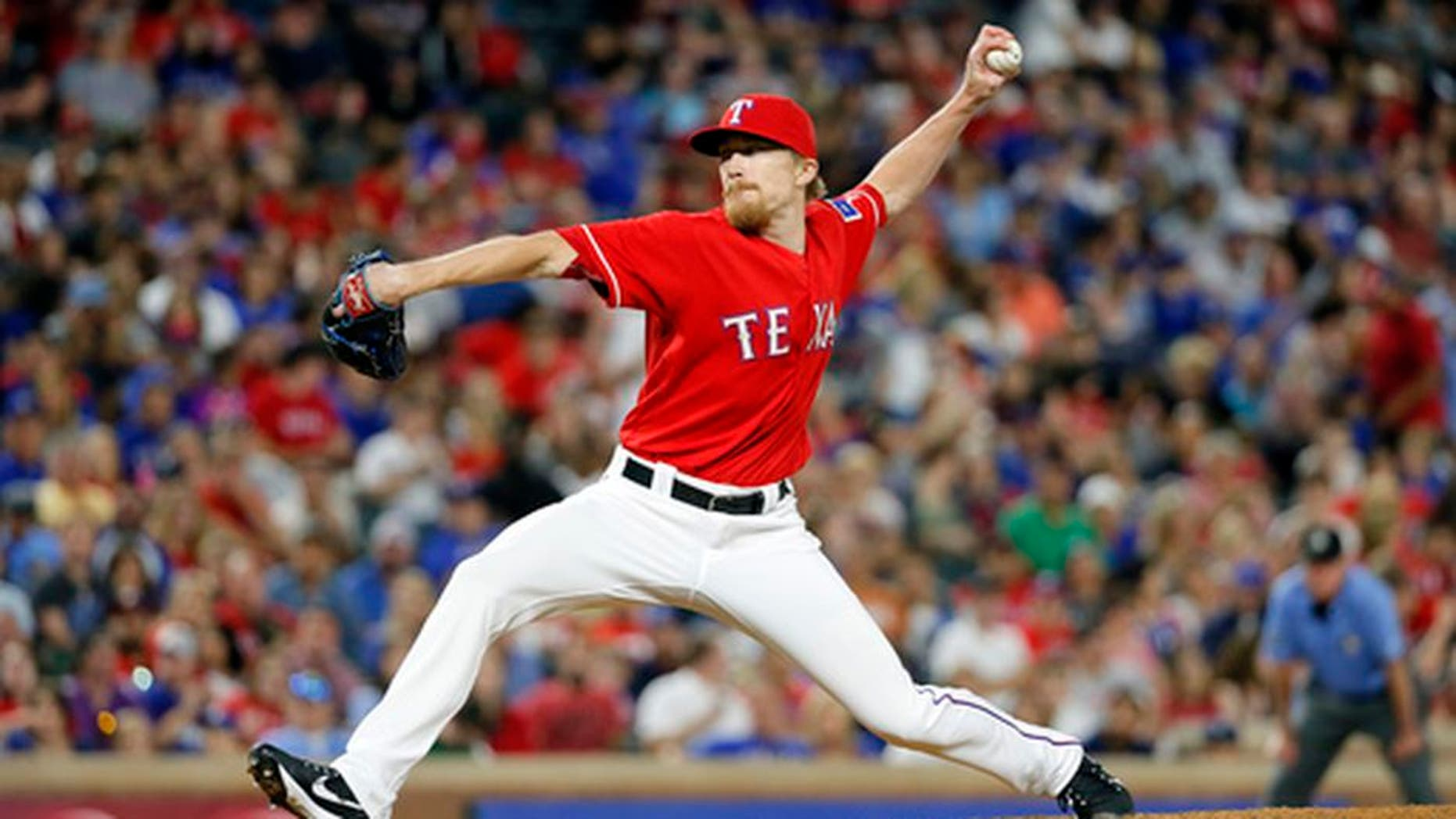 FILE - In this Sept. 30, 2016, file photo, Texas Rangers relief pitcher Jake Diekman throws to the Tampa Bay Ray during a baseball game in Arlington, Texas. Diekman is already counting the days until he can start throwing again, even though he still has another surgery in June. Diekman was back with his teammates Thursday, April 20, for the first time since the second of three operations to remove and rebuild his colon during treatment for the ulcerative colitis, a digestive condition he has dealt with much of his life. (AP Photo/Tony Gutierrez, File)