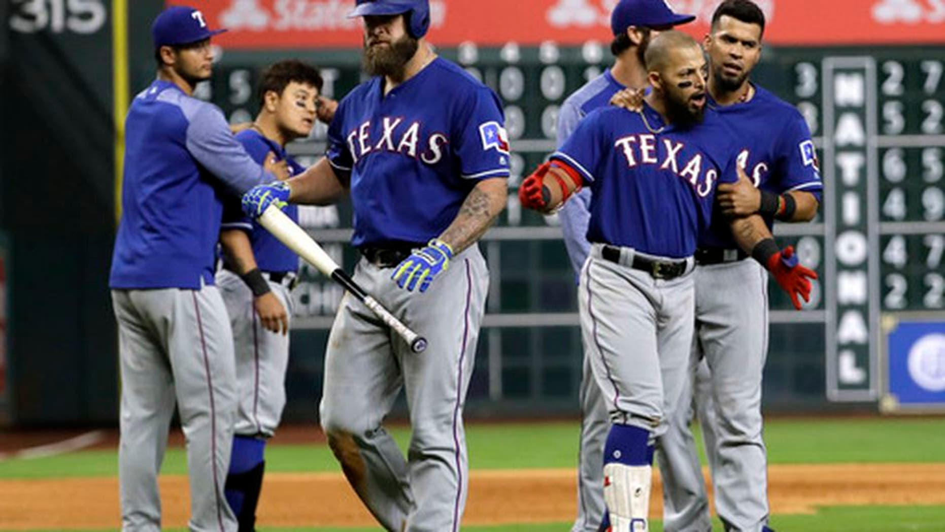 Texas Rangers' Mike Napoli, center, walks away as Rougned Odor, right, is restrained by Robinson Chirinos following a close pitch thrown by Houston Astros starting pitcher Lance McCullers Jr. to Napoli during the sixth inning of a baseball game, Monday, May 1, 2017, in Houston. (AP Photo/David J. Phillip)