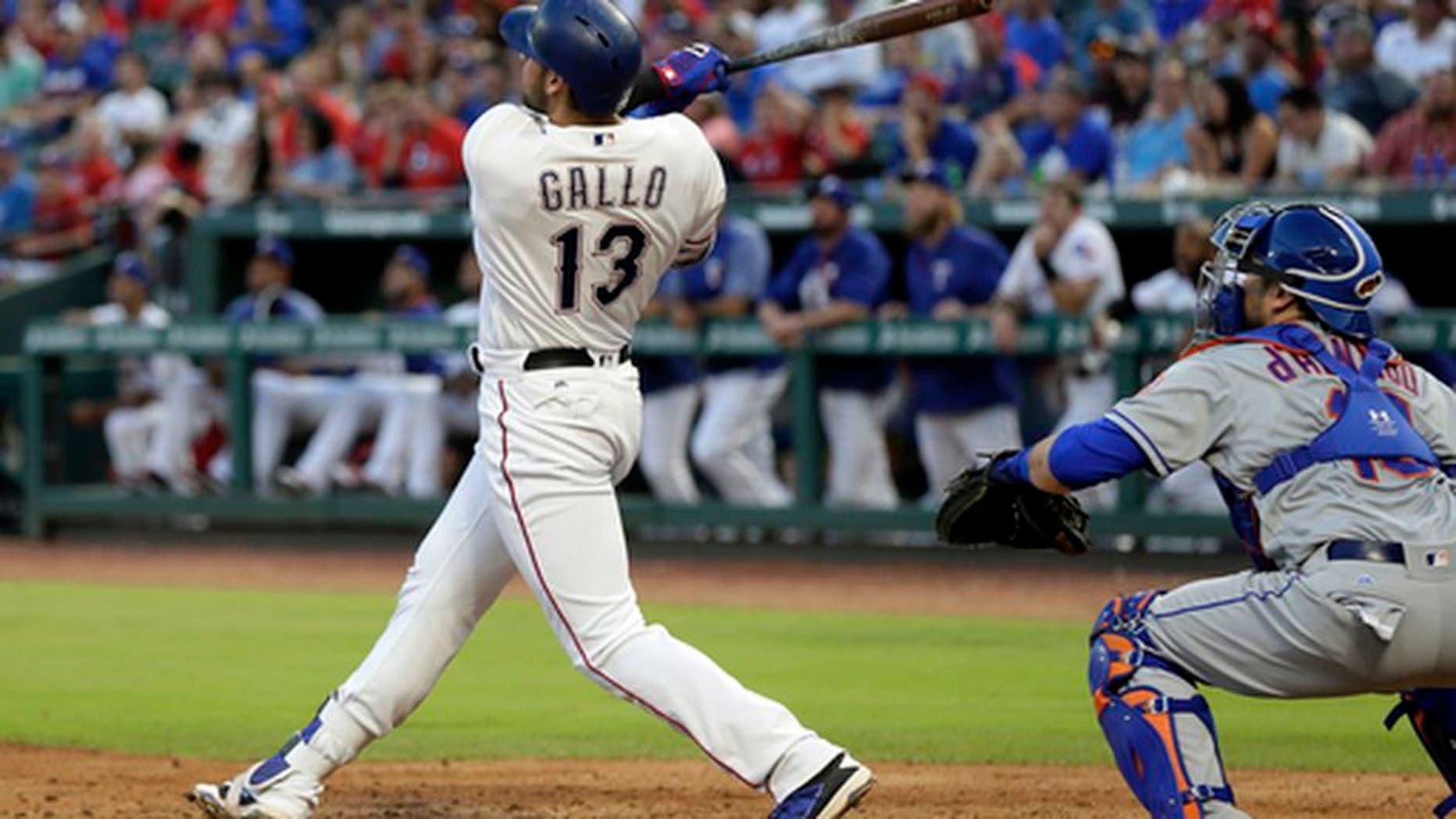 Texas Rangers' Joey Gallo (13) follows through on a two-run home run swing as New York Mets catcher Travis d'Arnaud watches in the third inning of an interleague baseball game, Tuesday, June 6, 2017, in Arlington, Texas. The shot scored Adrian Beltre in the 10-8 Rangers win. (AP Photo/Tony Gutierrez)