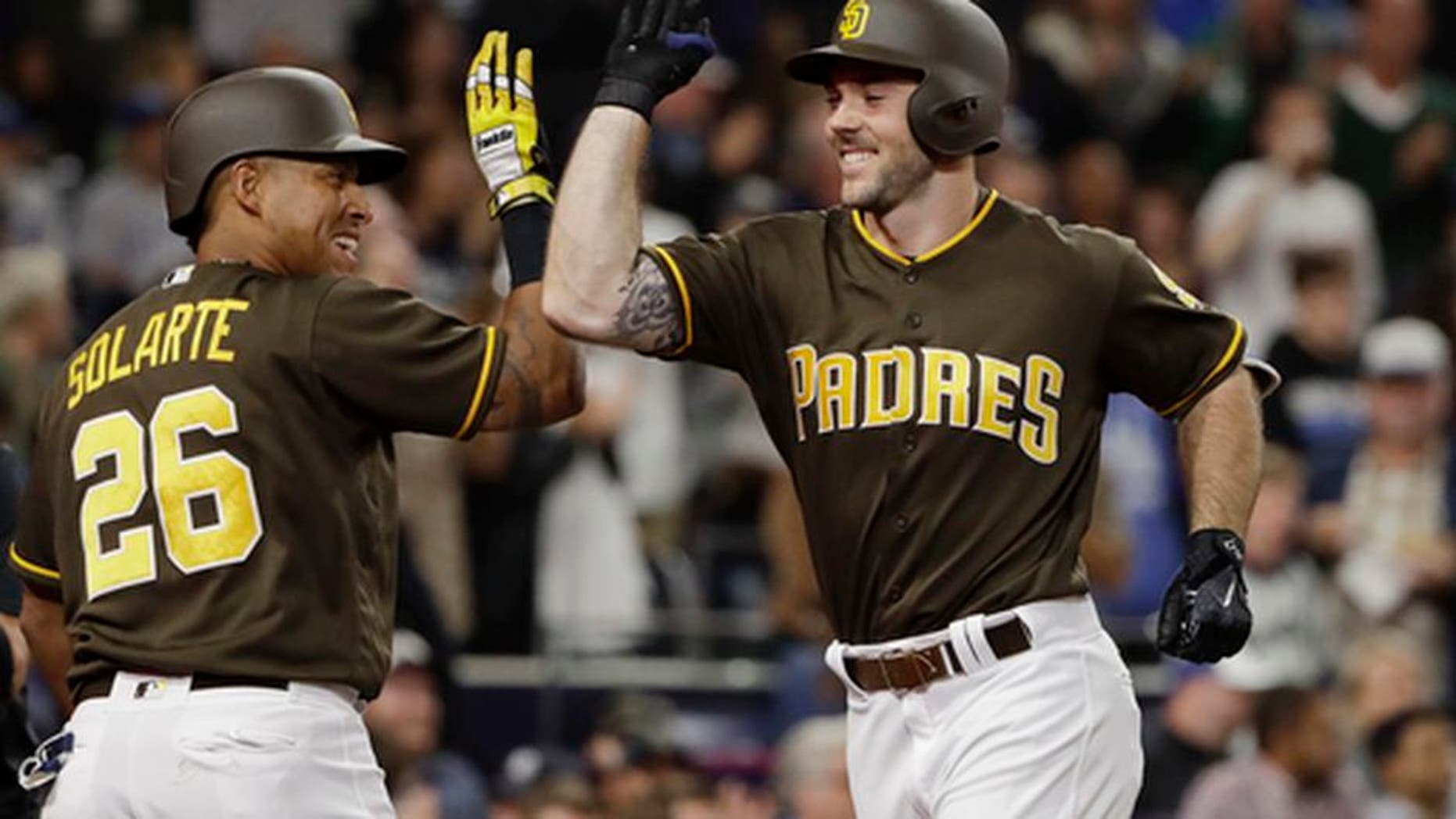 San Diego Padres' Matt Szczur, right, is greeted by Yangervis Solarte after hitting a home run during the seventh inning of the team's baseball game against the Kansas City Royals on Friday, June 9, 2017, in San Diego. (AP Photo/Gregory Bull)