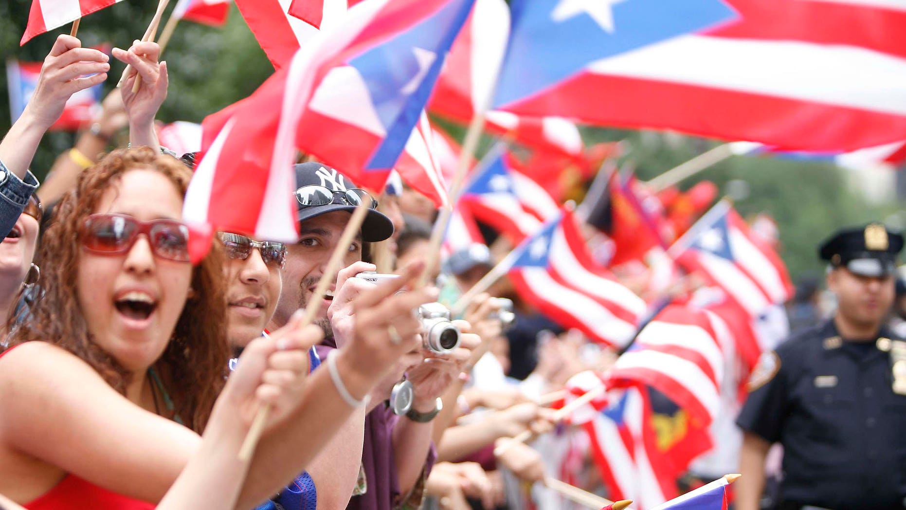 People wave flags during the 50th Anniversary of the National Puerto Rican Day Parade along 5th Avenue in 2007.