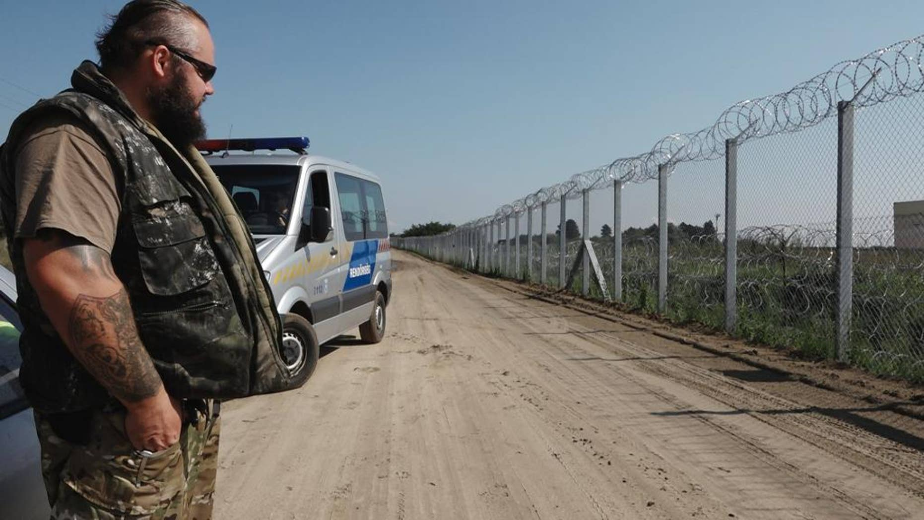 In this photo taken Wednesday, Sept. 14, 2016, ranger Zsolt Takacs guards the fence on Hungary's border with Serbia, built last year to stop the flow of migrants and refugees from entering the country. Hungary, concerned that a new surge of migrants trying to reach the European Union could soon take place, is planning to reinforce the barrier with a new fence and surveillance equipment. (AP Photo/Andras Nagy)