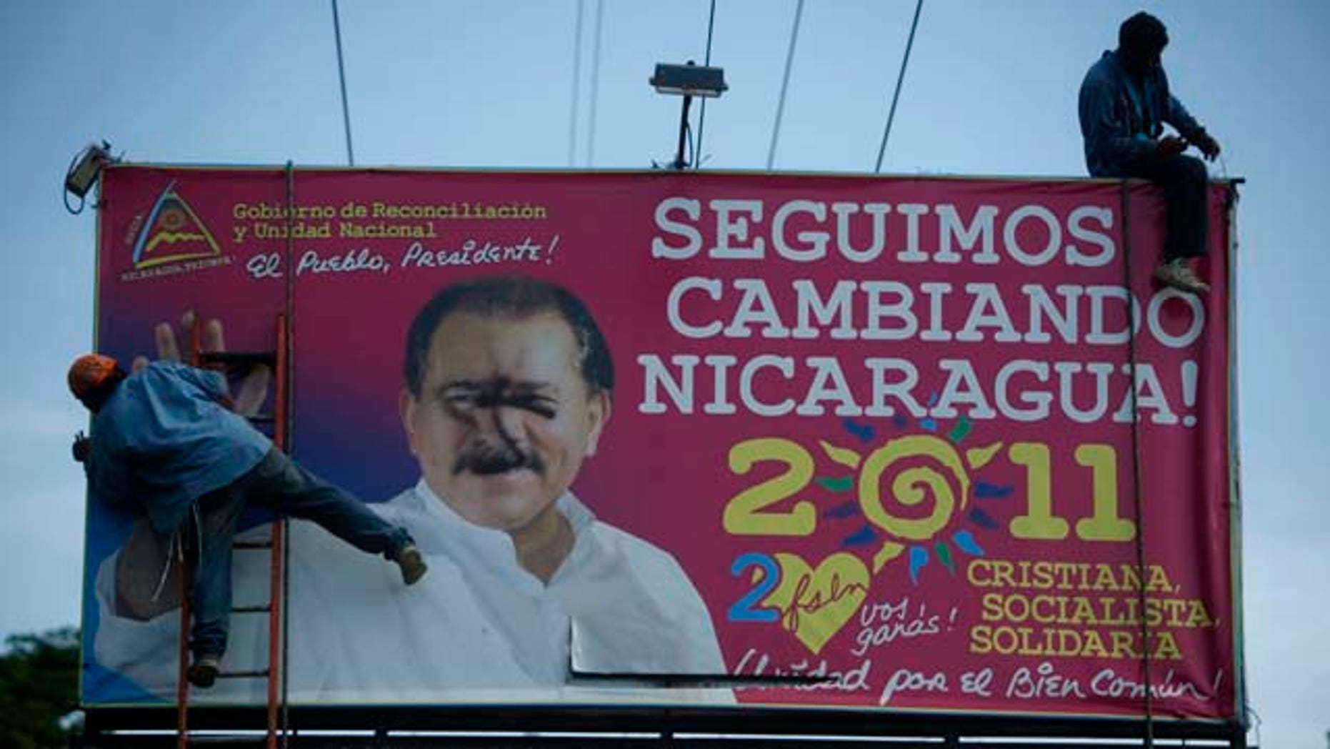 "Workers remove a billboard with political propaganda supporting Nicaragua's current President Daniel Ortega that reads in Spanish ""We keep changing Nicaragua: Christian, socialist, with solidarity"" in Managua, Nicaragua, Thursday, Aug. 18, 2011. Religious processions and chants have become common in the re-election campaign rallies of leftist Nicaraguan President Daniel Ortega, who is highlighting his Christianity in his latest bid for presidency. (AP Photo/Esteban Felix)"