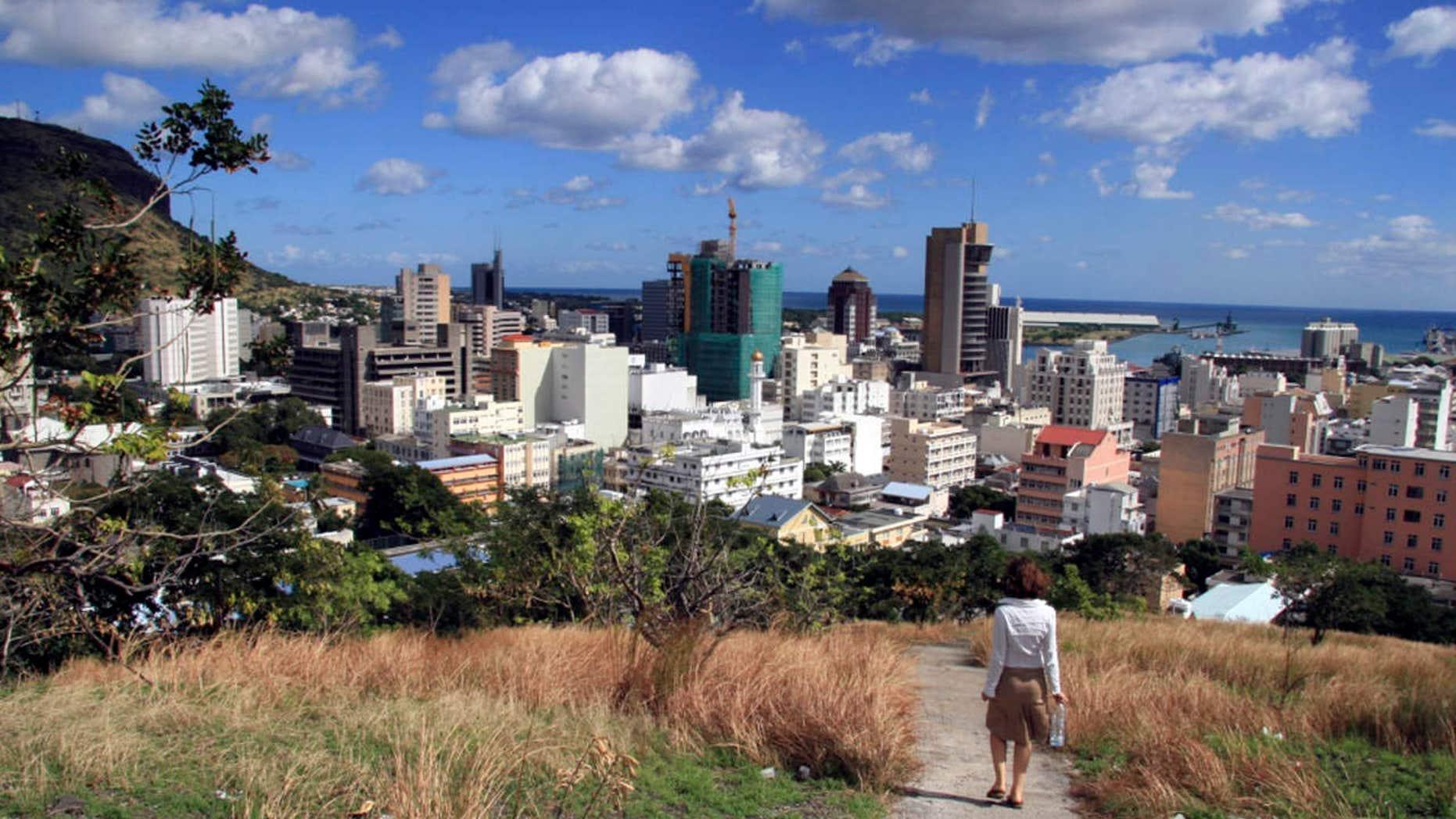 A woman walks down a hill to Port Louis, Mauritius