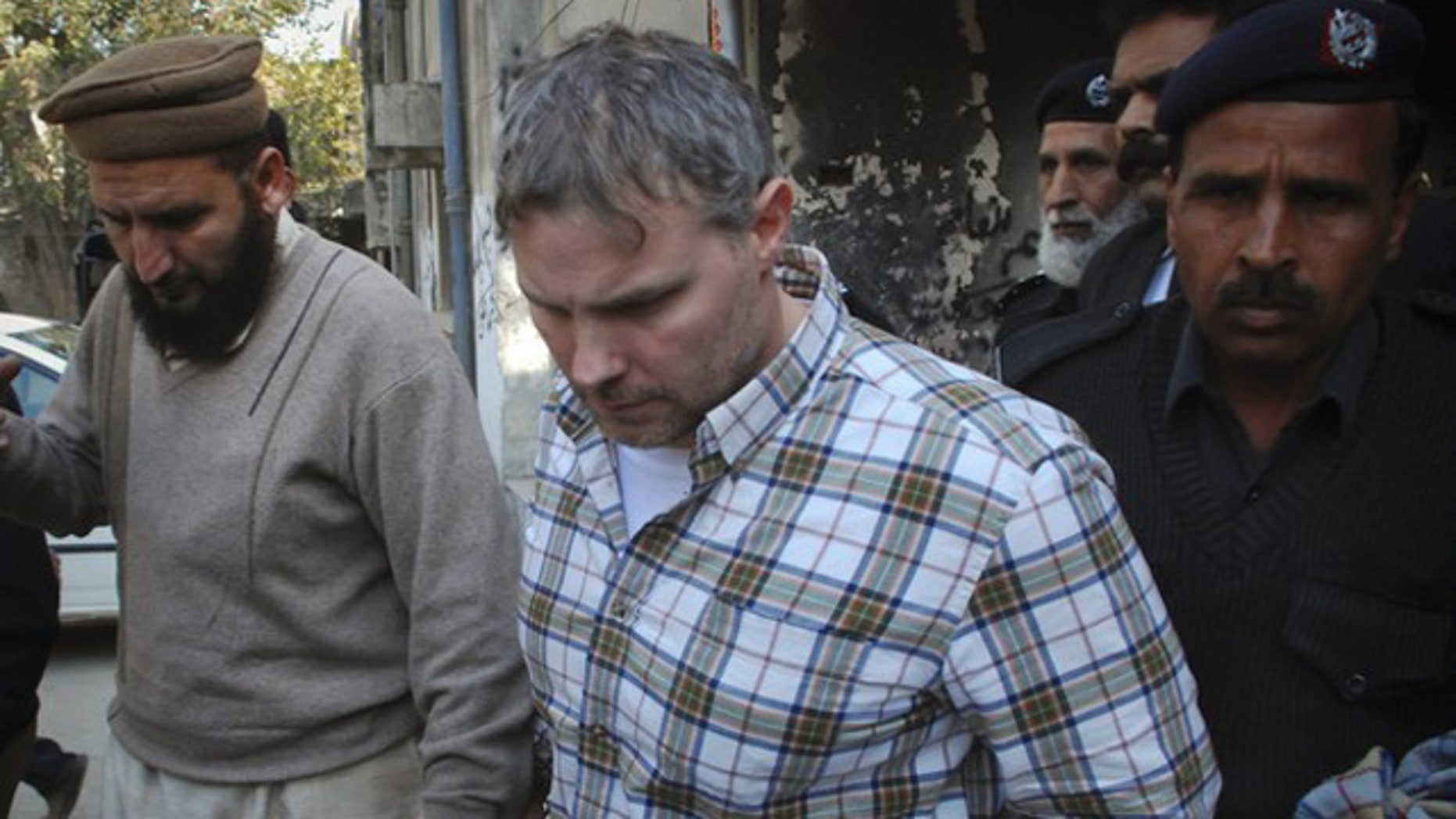 Jan. 28: A U.S. consulate employee is escorted by police and officials out of court after facing a judge in Lahore.
