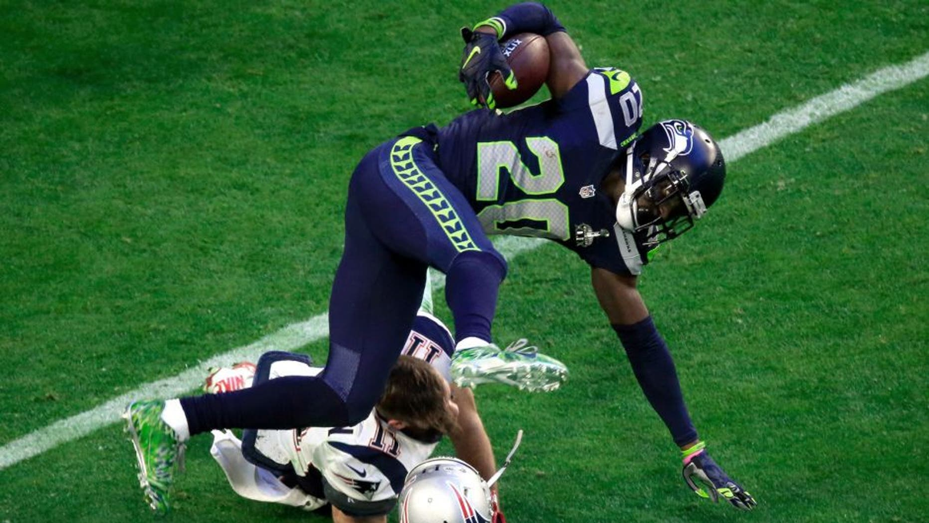 GLENDALE, AZ - FEBRUARY 01: Julian Edelman #11 of the New England Patriots tackles Jeremy Lane #20 of the Seattle Seahawks after an interception in the first quarter during Super Bowl XLIX at University of Phoenix Stadium on February 1, 2015 in Glendale, Arizona. (Photo by Jamie Squire/Getty Images)