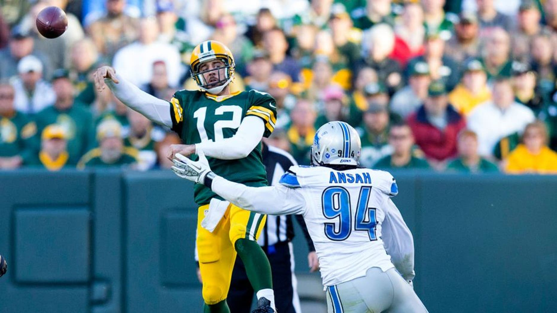 Nov 15, 2015; Green Bay, WI, USA; Green Bay Packers quarterback Aaron Rodgers (12) throws a pass under pressure from Detroit Lions defensive end Ezekiel Ansah (94) during the fourth quarter at Lambeau Field. Detroit won 18-16. Mandatory Credit: Jeff Hanisch-USA TODAY Sports