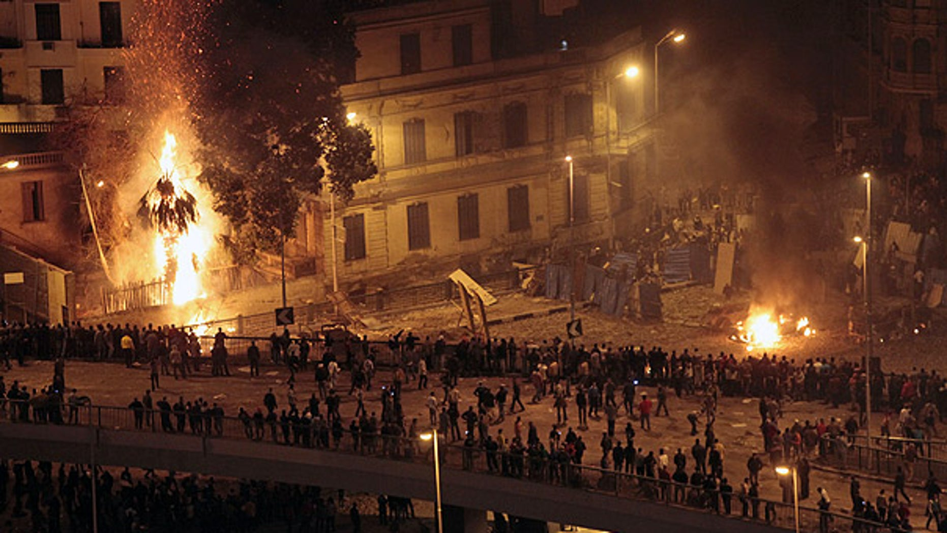 Feb. 3: Pro-Mubarak demonstrators, bottom, clash with anti-government demonstrators, top right, as a palm tree burns from a firebomb, in Tahrir Square, Cairo.