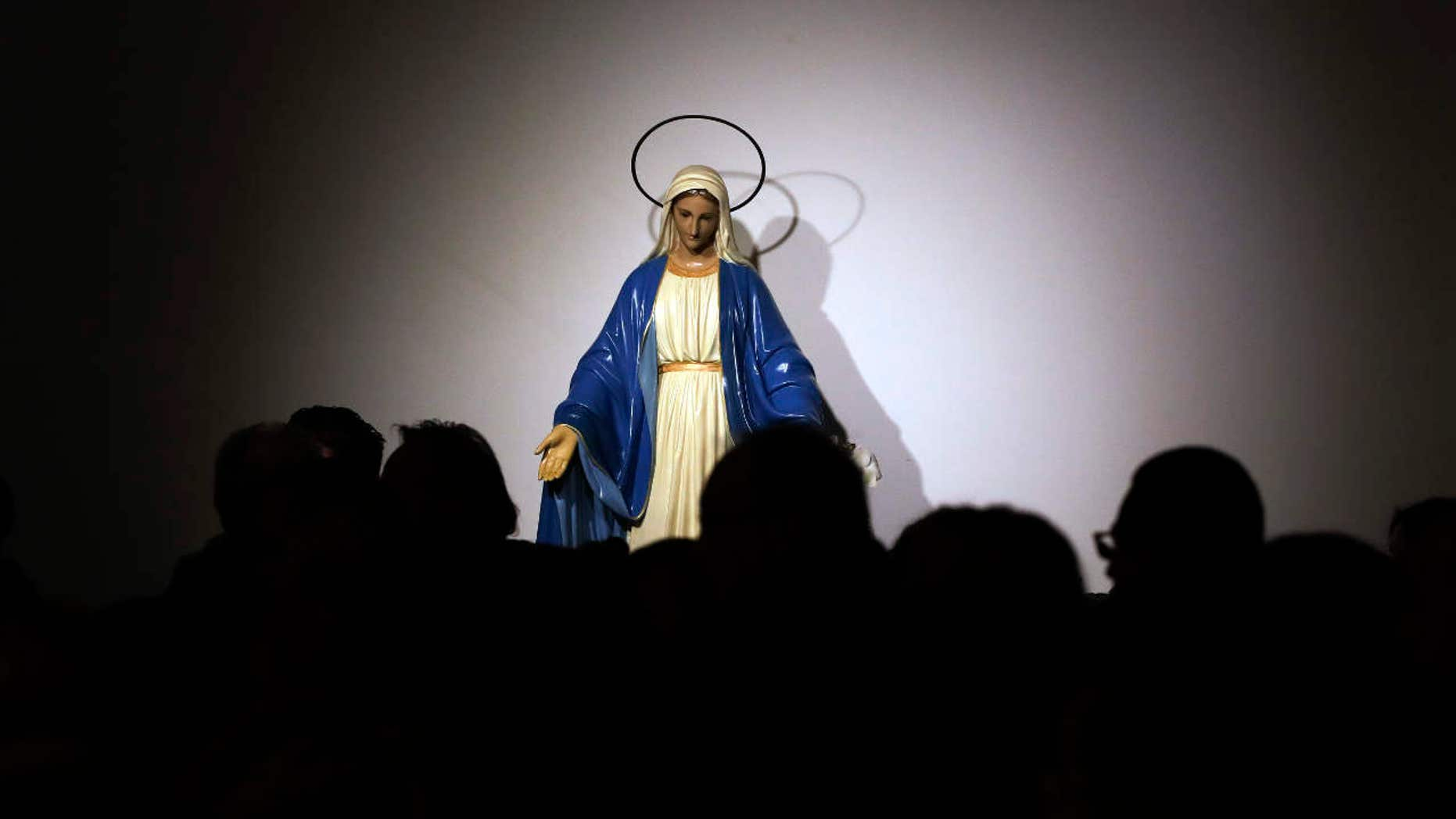 A statue of the Virgin Mary is seen in background as faithful attend a Mass celebrated by Pope Francis at the St. Mary of Setteville di Guidonia parish church, in the outskirts of Rome, Sunday, Jan. 15, 2017.