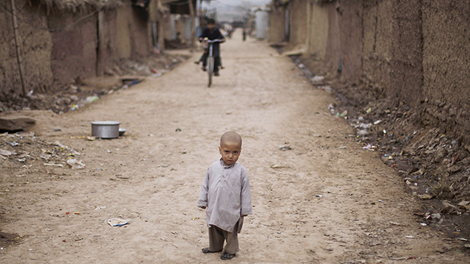 Feb. 3: A young Afghan refugee boy looks on as he stands in an alley in a slum on the outskirts of Islamabad, Pakistan.