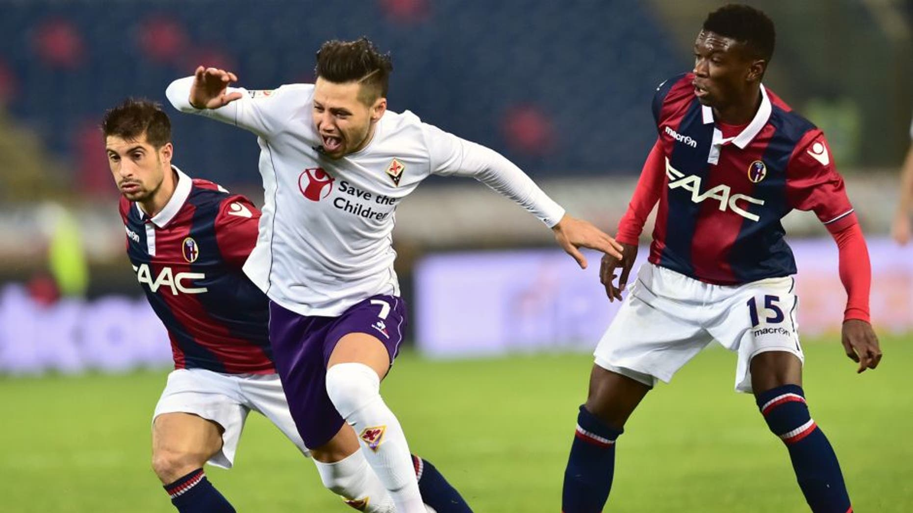 """Fiorentina's forward from Argentina Mauro Zarate (C) fights for the ball with Bologna's defender from Senegal Ibrahima Mbaye and Bologna's forward from Italy Franco Brienza (L) during the Italian Serie A football match Bologna vs Fiorentina at """"Renato Dall'Ara"""" Stadium in Bologna on Febrauary 6, 2016. / AFP / GIUSEPPE CACACE (Photo credit should read GIUSEPPE CACACE/AFP/Getty Images)"""