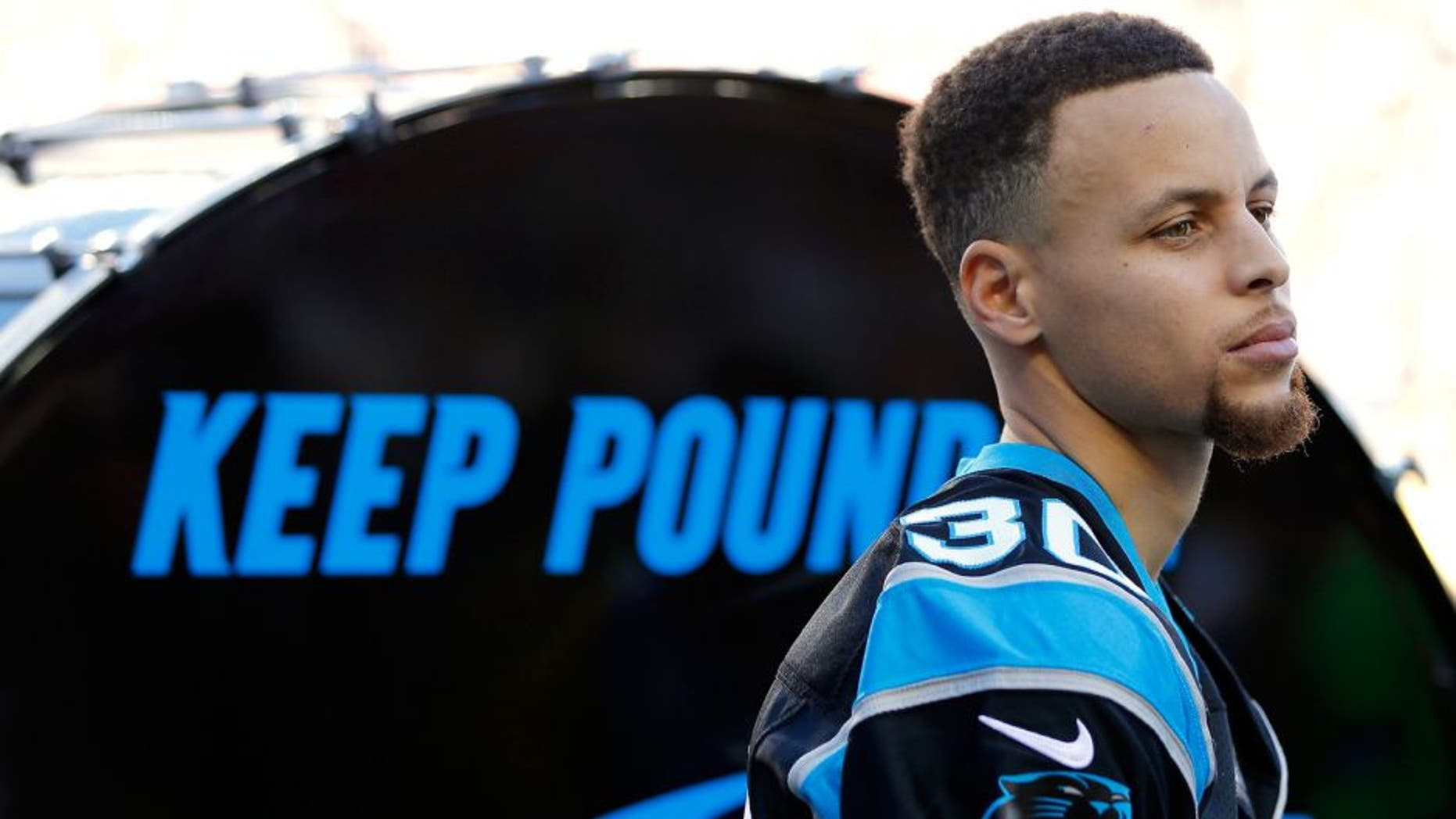 """SANTA CLARA, CA - FEBRUARY 07: Stephen Curry of the Golden State Warriors prepares to hit the """"Keep Pounding"""" drum for the Carolina Panthers prior to Super Bowl 50 against the Denver Broncos at Levi's Stadium on February 7, 2016 in Santa Clara, California. (Photo by Kevin C. Cox/Getty Images)"""