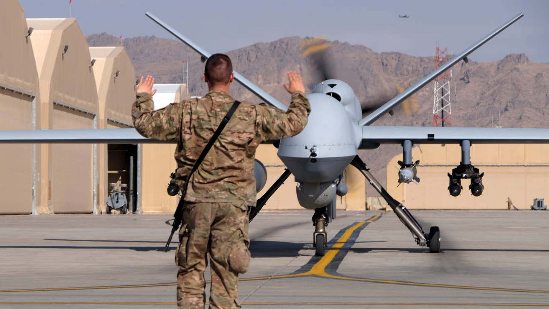 A U.S. airman guides a U.S. Air Force MQ-9 Reaper drone as it taxis to the runway at Kandahar Airfield