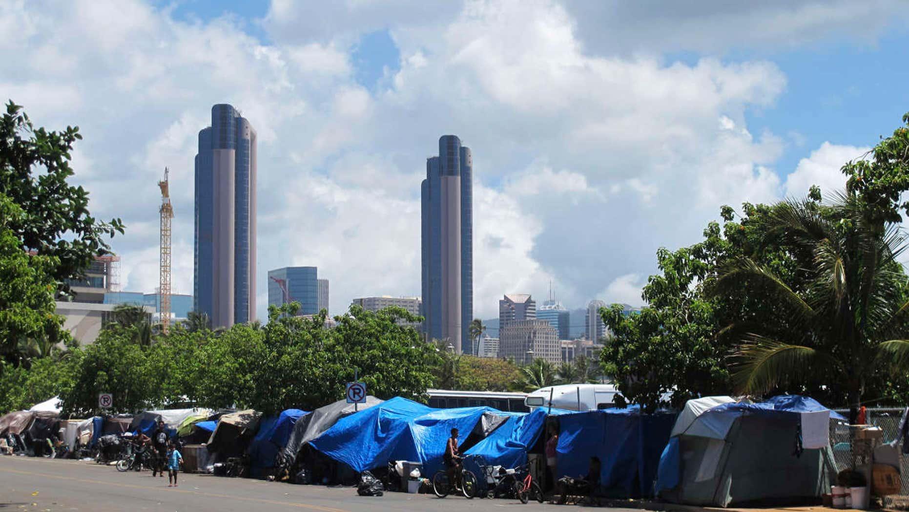 FILE - In this June 30, 2015, file photo, people camp out on a sidewalk in the Kakaako neighborhood of Honolulu, Hawaii.
