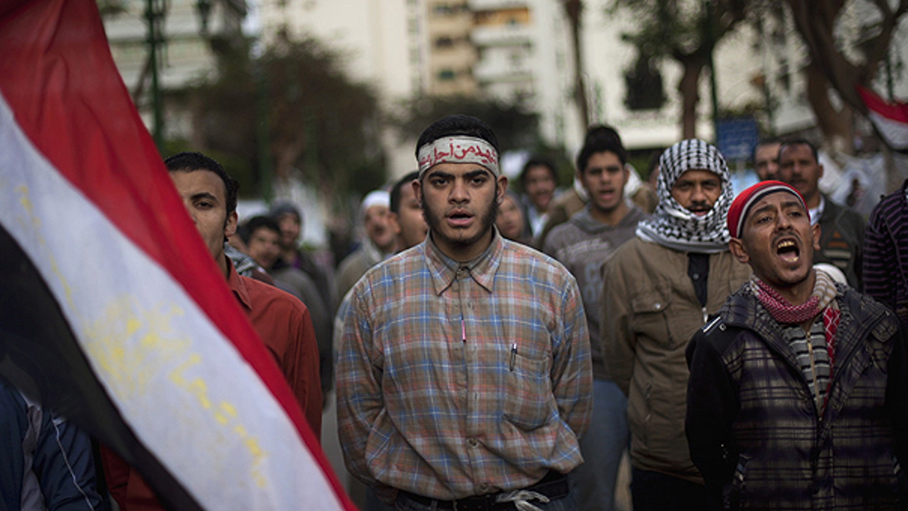 Feb. 10: Anti-government protesters shout slogans as they line up after spending the night in front of the Egyptian Parliament in Cairo, Egypt.