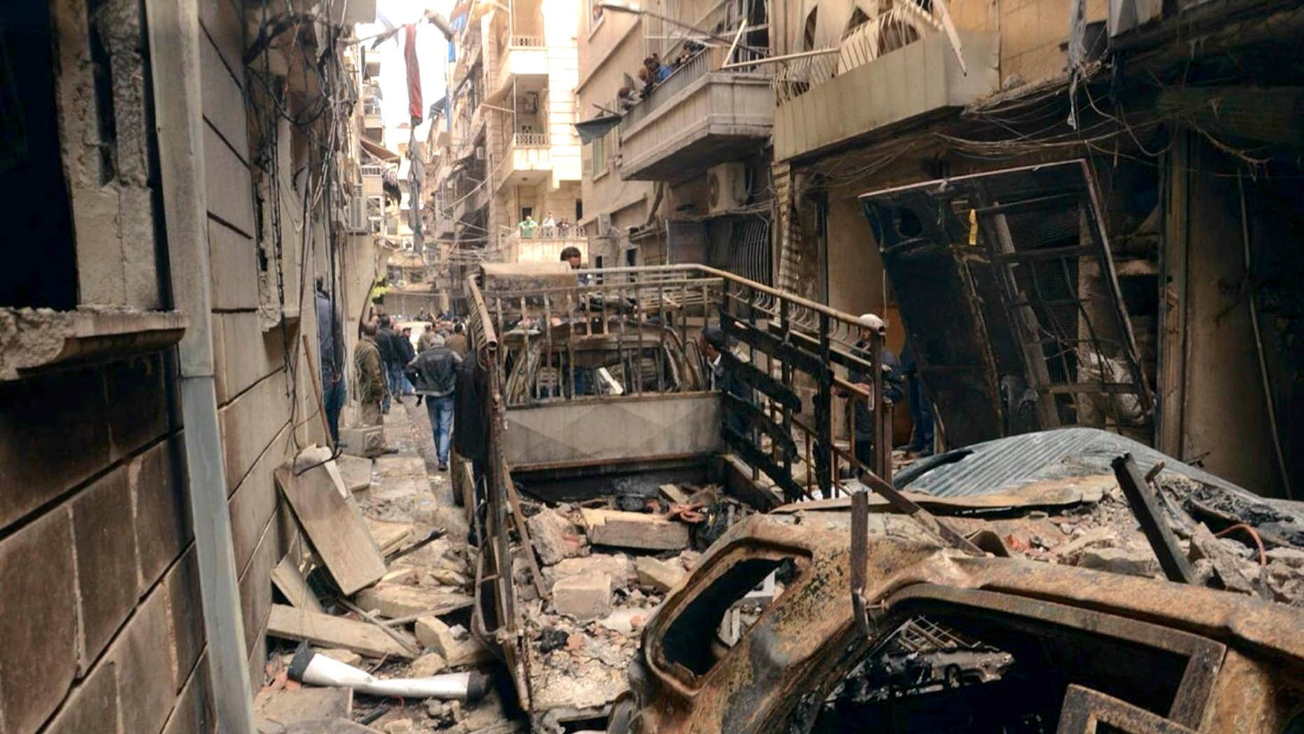 April 11, 2015: In this photo released by the Syrian official news agency SANA, Syrians gather in a street that was hit by shelling, in the predominantly Christian and Armenian neighborhood of Suleimaniyeh, Aleppo, Syria.