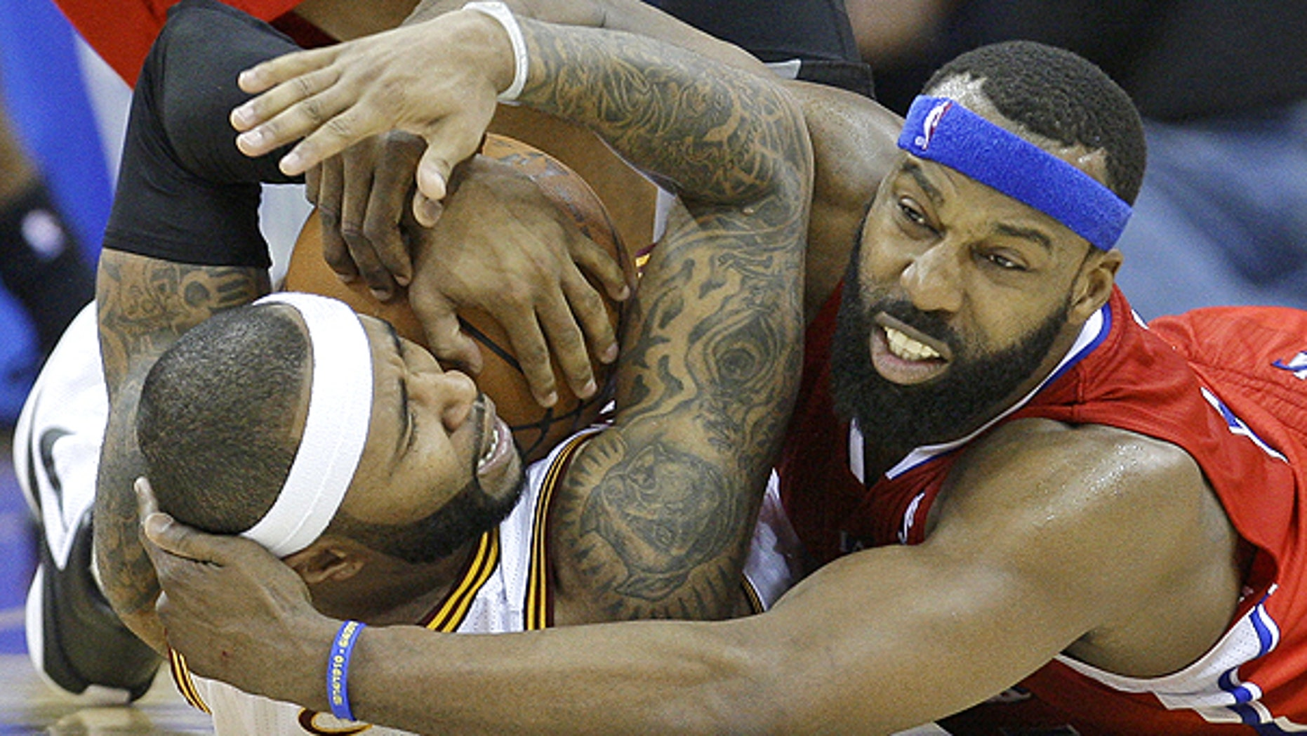 Feb. 11: Cleveland Cavaliers' Mo Williams, left, holds onto the basketball as Los Angeles Clippers' Baron Davis, right, tries to pry it loose in overtime in an NBA game in Cleveland.