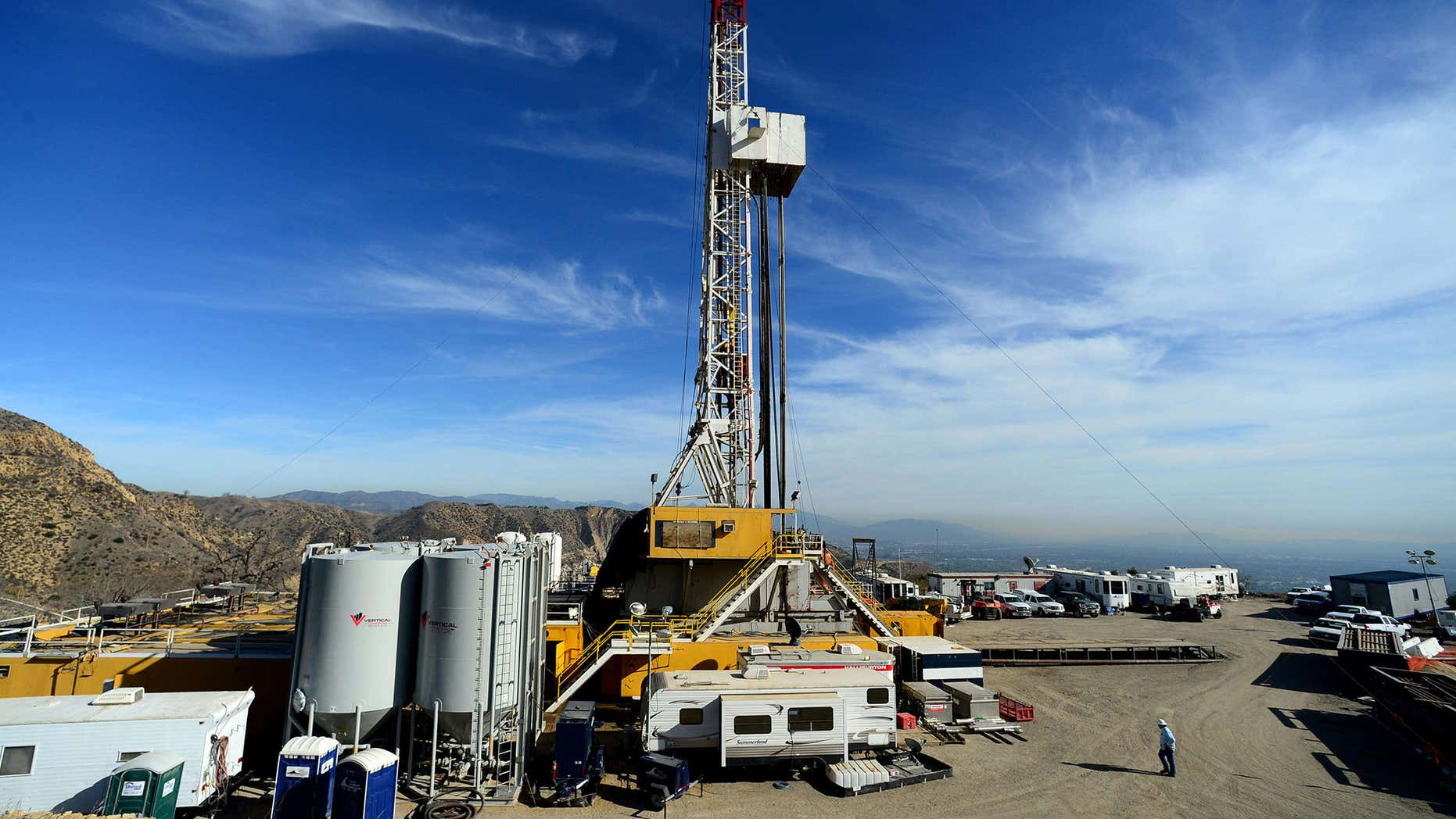 FILE - In this Dec. 9, 2015, pool file photo, crews work on stopping a gas leak at a relief well at the Aliso Canyon facility above the Porter Ranch area of Los Angeles.